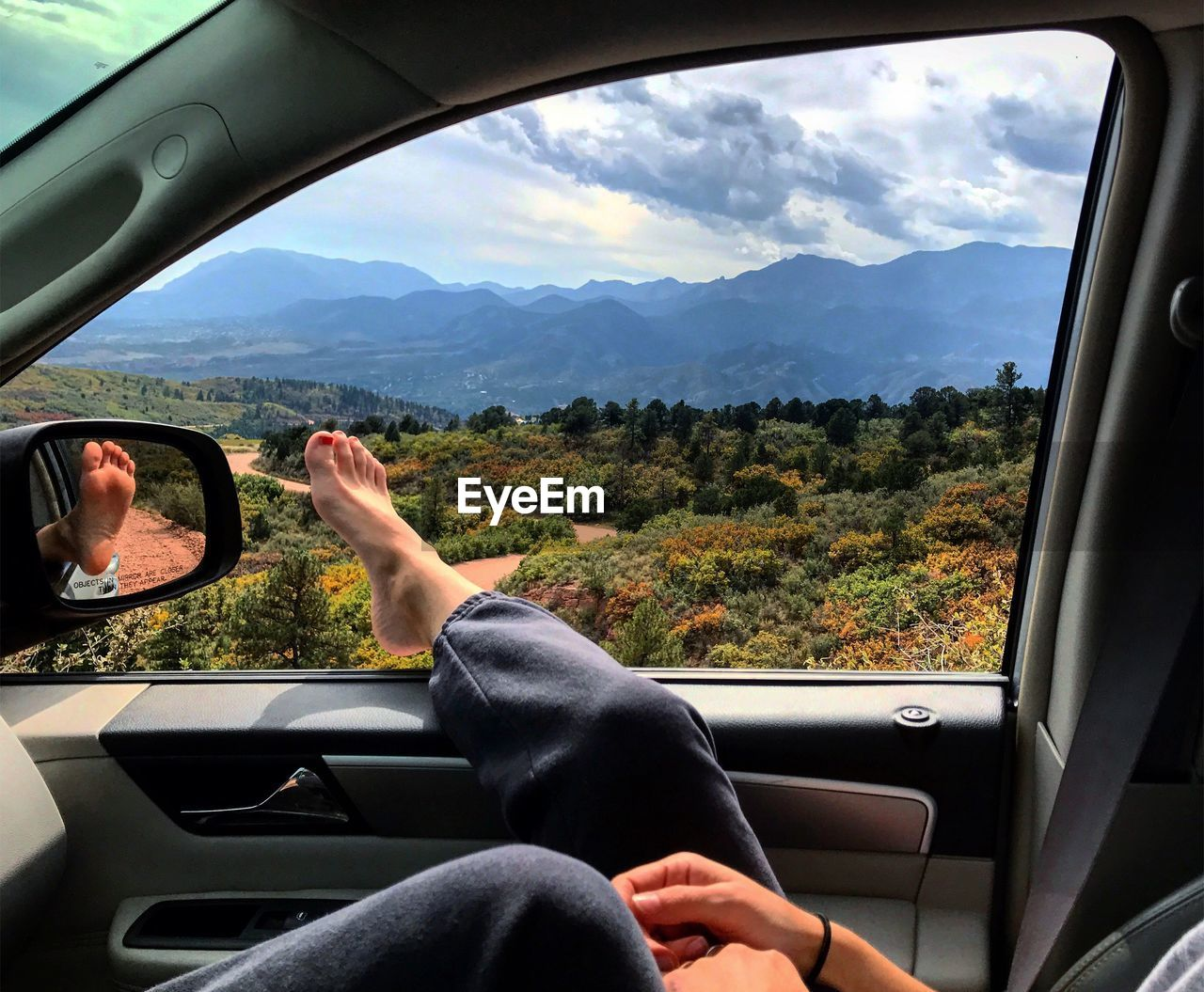 Low Section Of Woman Resting Leg On Car Window