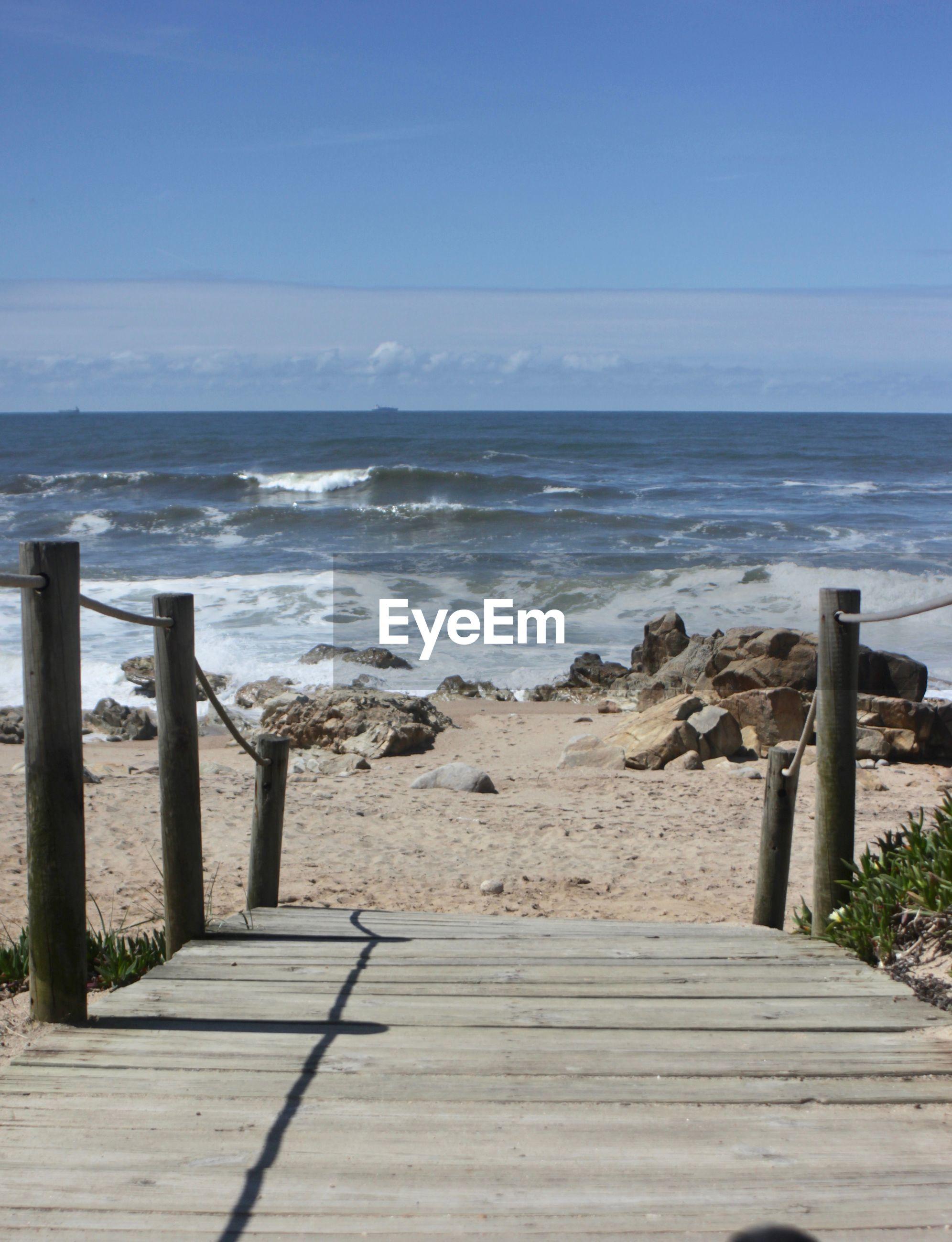 WOODEN POST ON BEACH AGAINST SKY