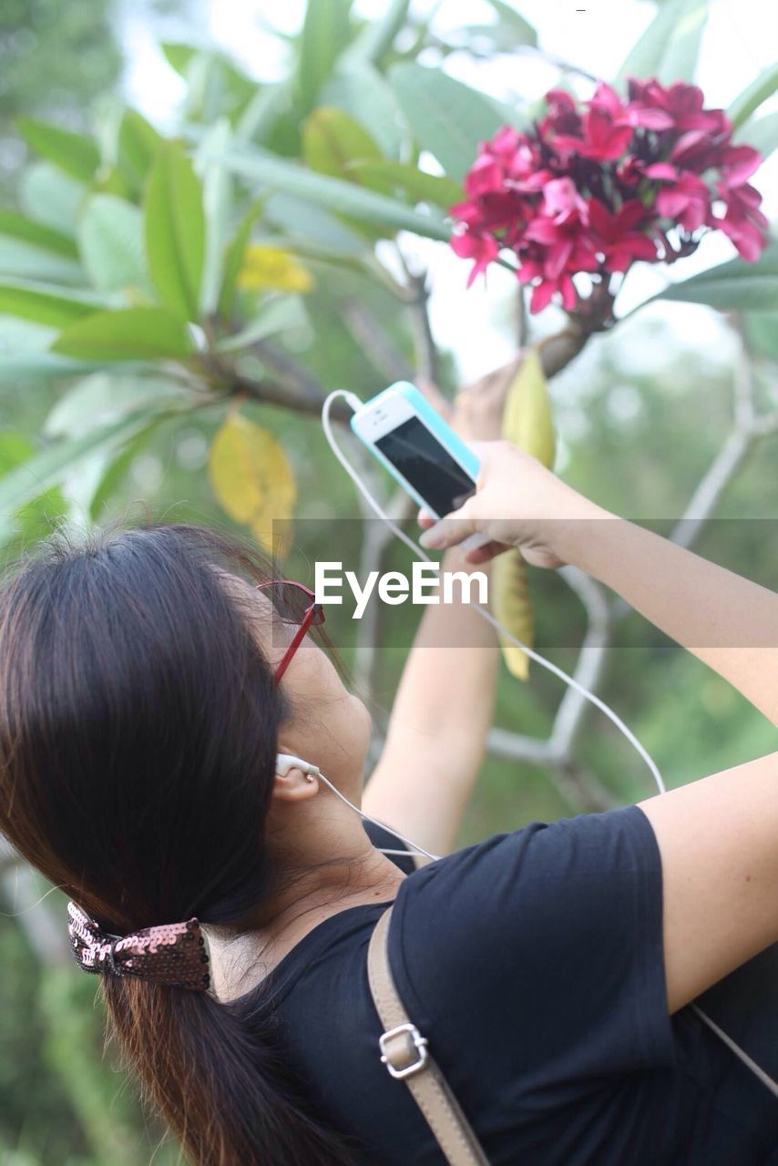 Tilt Image Of Woman Photographing Flower Through Cell Phone
