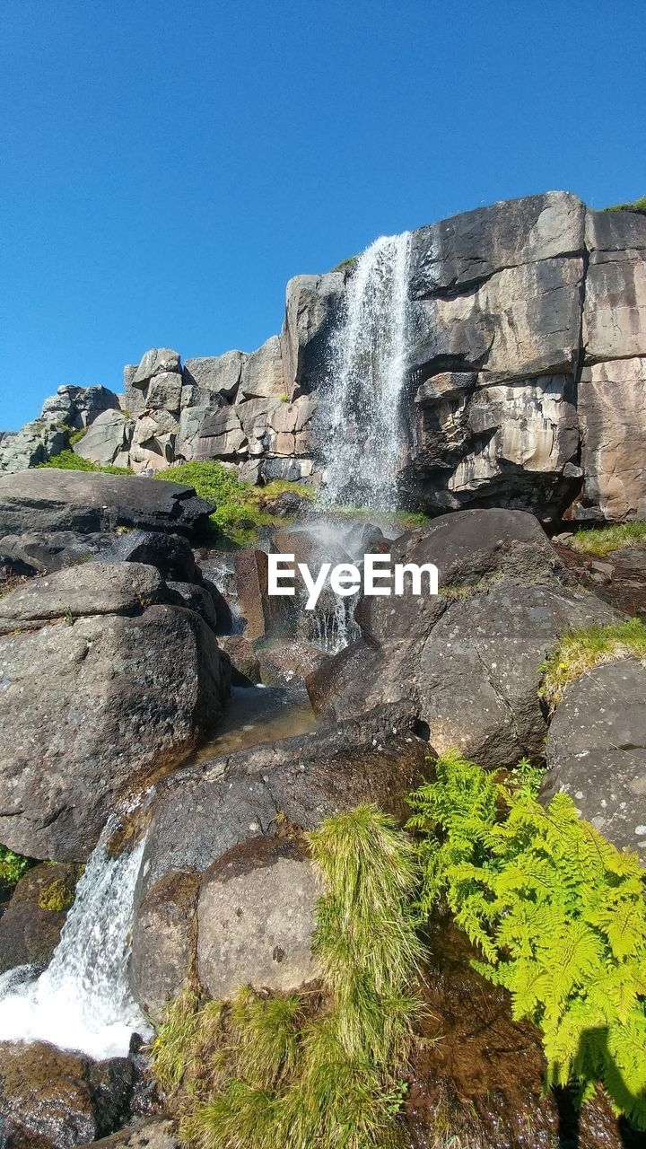 water, rock, waterfall, nature, sky, rock - object, beauty in nature, motion, scenics - nature, solid, rock formation, long exposure, clear sky, day, flowing water, splashing, no people, land, blurred motion, outdoors, flowing, power in nature, formation, falling water