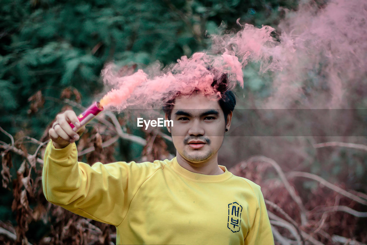 Portrait of young man holding distress flare against tree