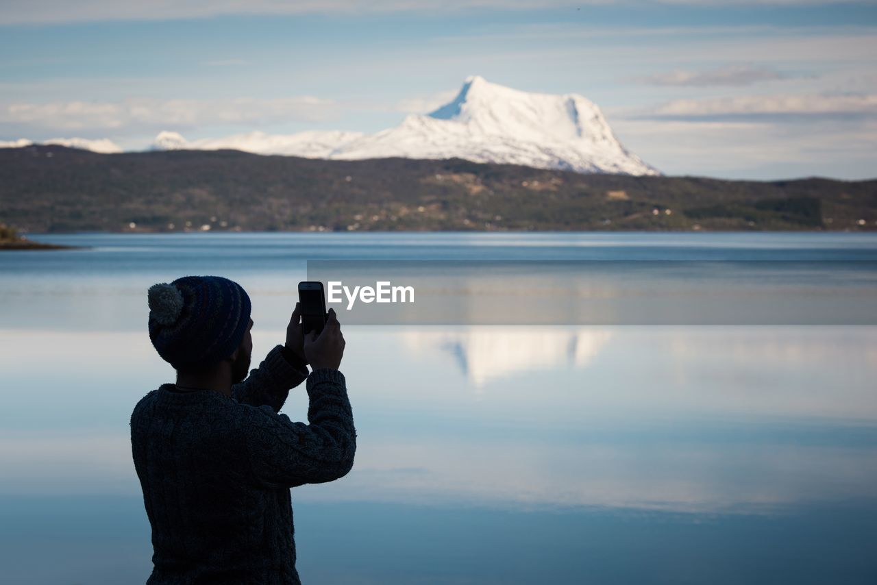 REAR VIEW OF WOMAN PHOTOGRAPHING BY LAKE AGAINST MOUNTAIN