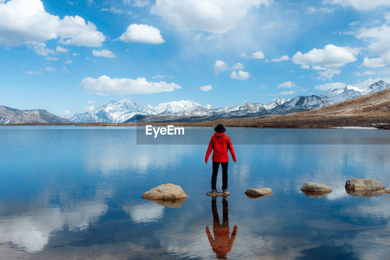 cloud - sky, water, rear view, scenics - nature, sky, mountain, beauty in nature, one person, tranquil scene, lake, reflection, full length, standing, tranquility, nature, real people, day, mountain range, idyllic