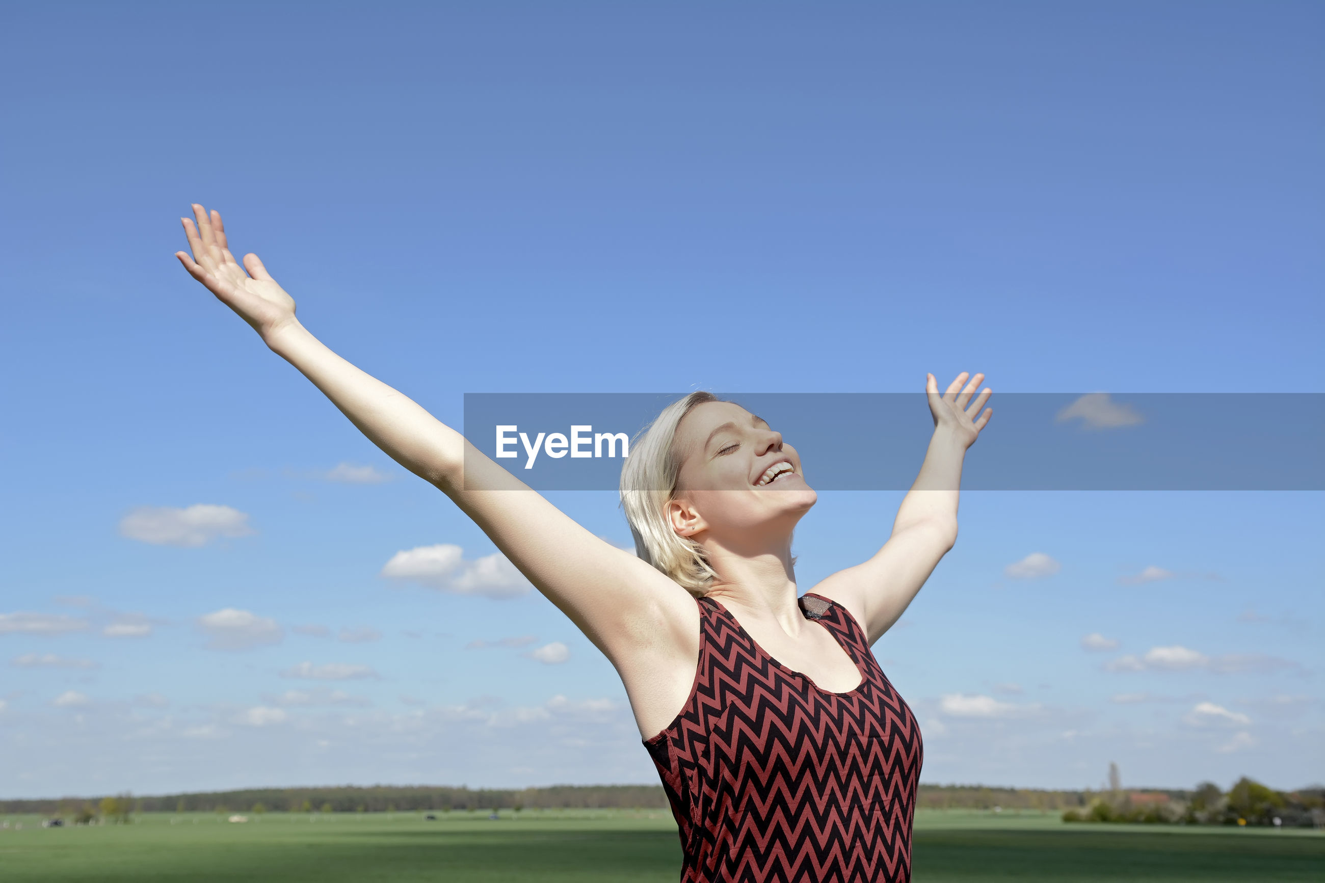 Smiling young woman with arms outstretched standing on landscape against blue sky