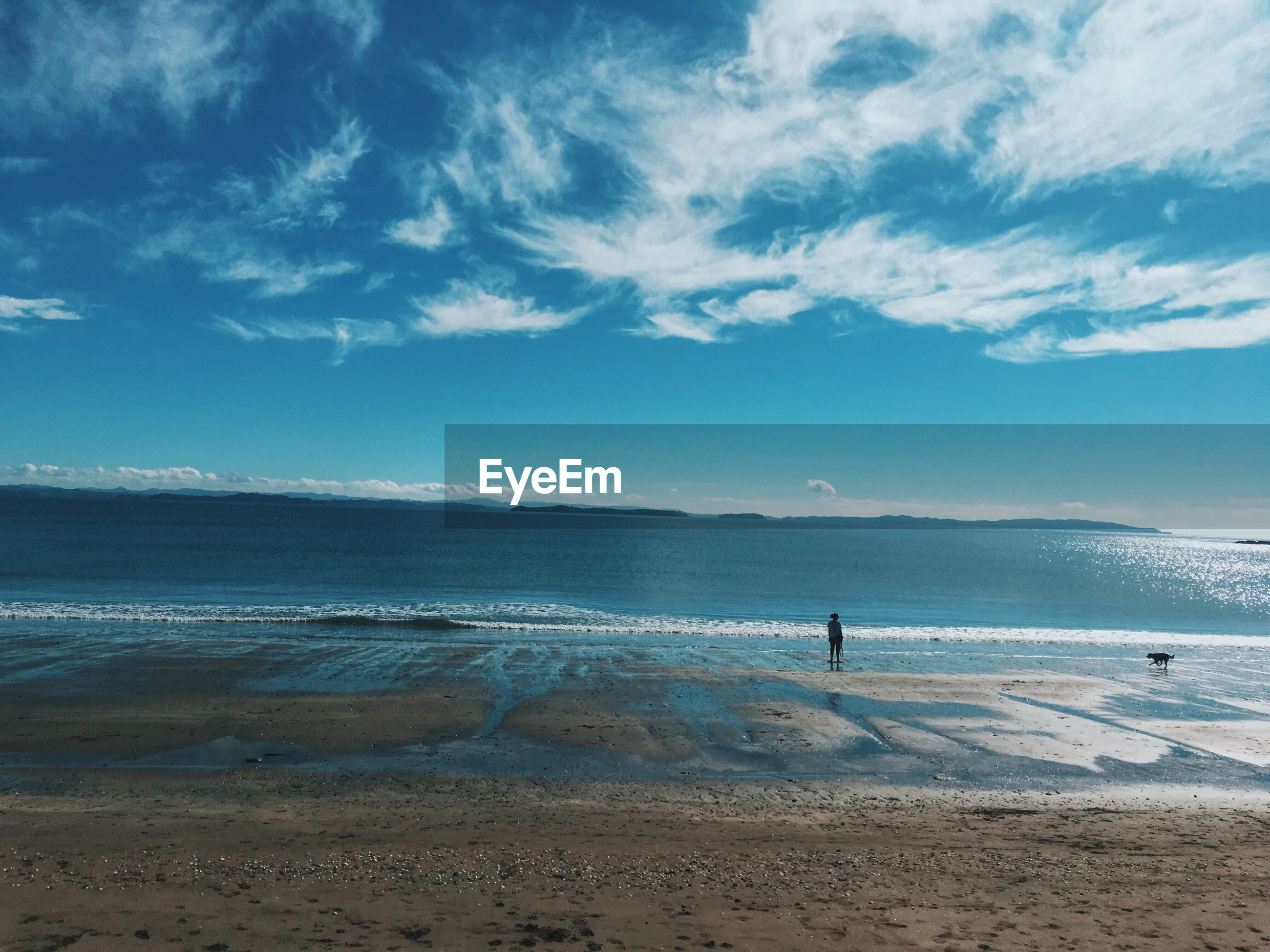 beach, water, tranquil scene, scenics, sky, tranquility, sand, sea, mountain, shore, beauty in nature, blue, coastline, vacations, nature, tourism, solitude, non-urban scene, remote, cloud - sky, travel destinations, calm, outdoors, summer, day, distant, mountain range