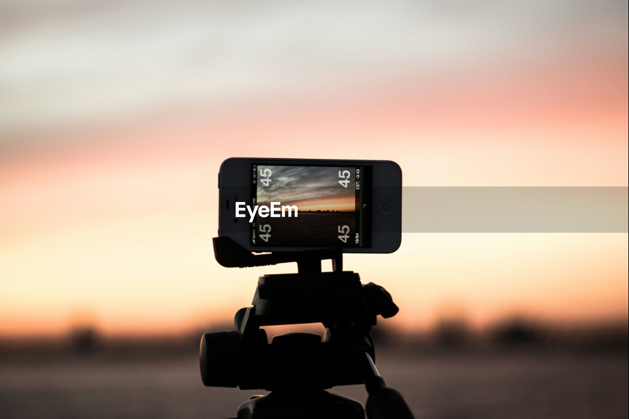 sunset, technology, photography themes, focus on foreground, silhouette, camera - photographic equipment, photographing, wireless technology, close-up, orange color, sky, communication, digital camera, holding, smart phone, connection, one person, nature, tranquility, mobile phone