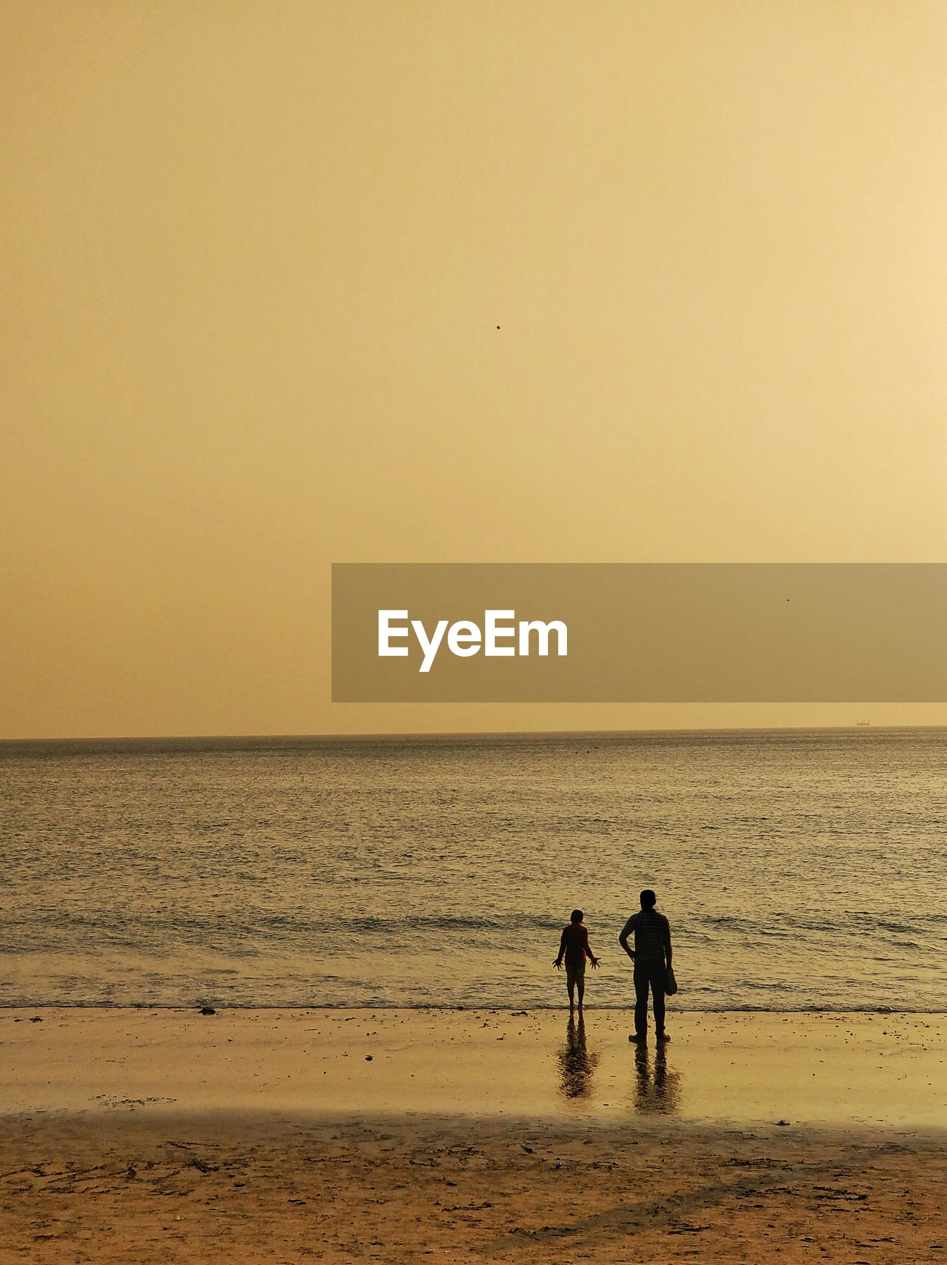 Silhouette man with son standing on shore at beach against clear orange sky