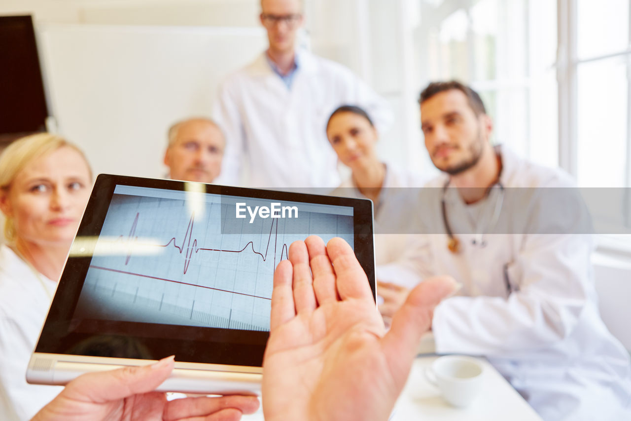 Cropped Hands Of Doctor Explaining Pulse Trace With Tablet To Colleague In Hospital