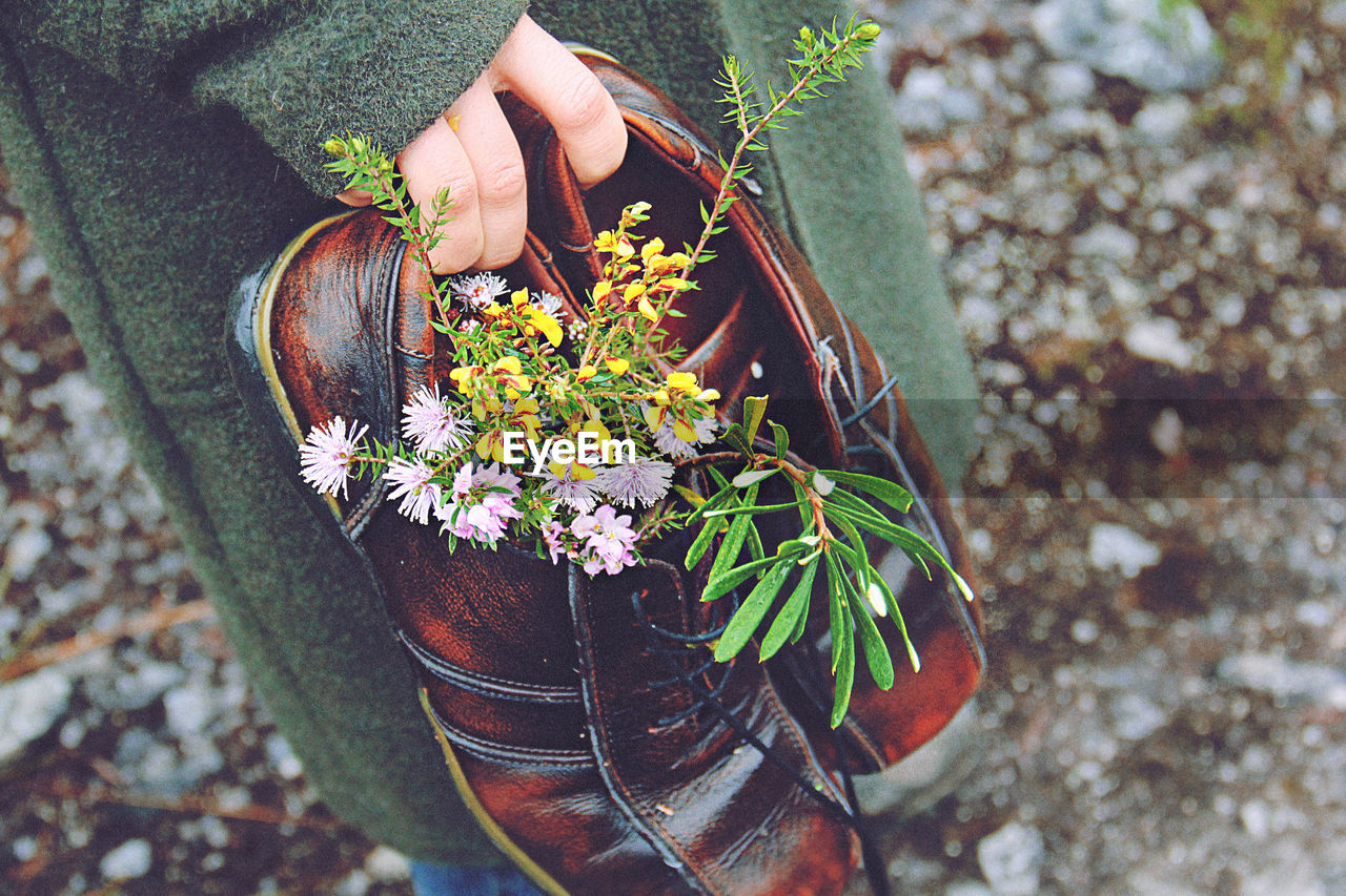 Midsection Of Person Holding Shoes With Flowers On Field