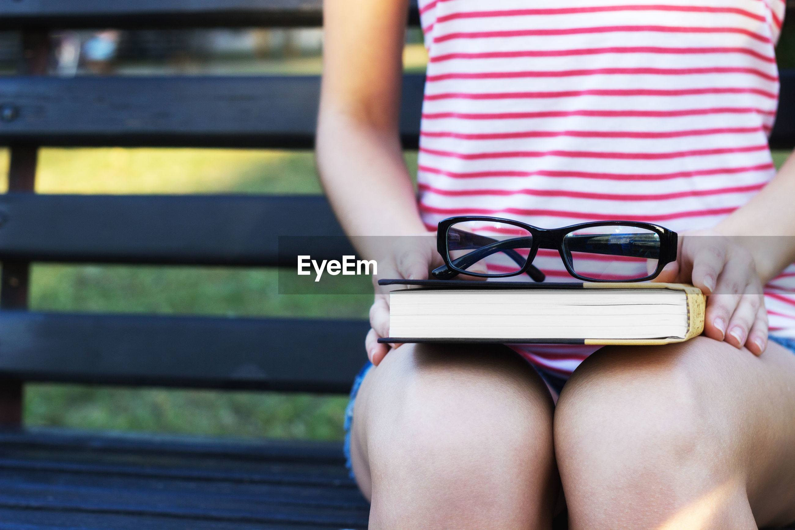 Midsection of woman holding book and eyeglasses while sitting on bench in park