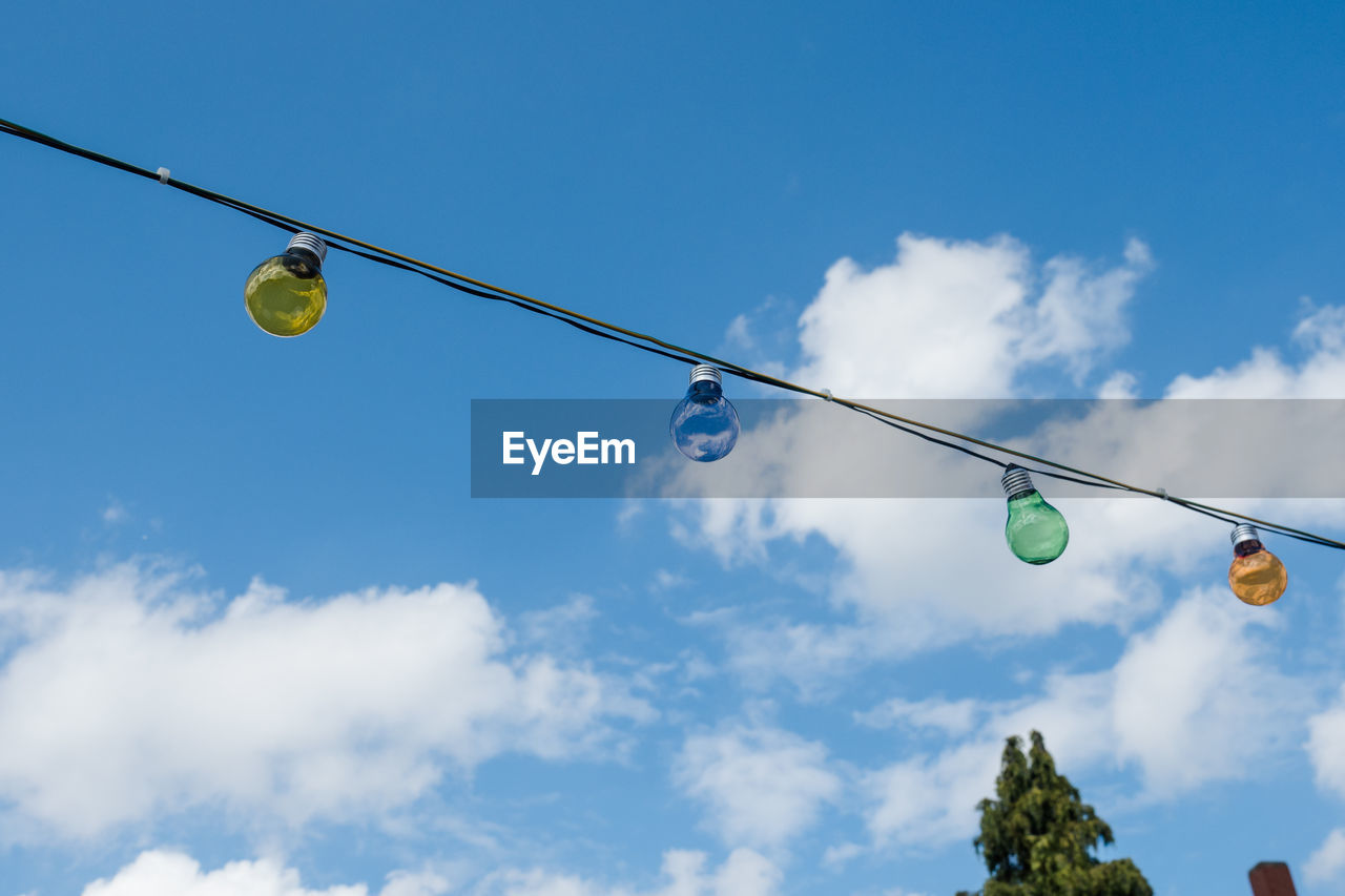 sky, low angle view, hanging, cloud - sky, blue, nature, no people, lighting equipment, yellow, day, light bulb, cable, decoration, outdoors, balloon, string, celebration, sunlight, green color, ball