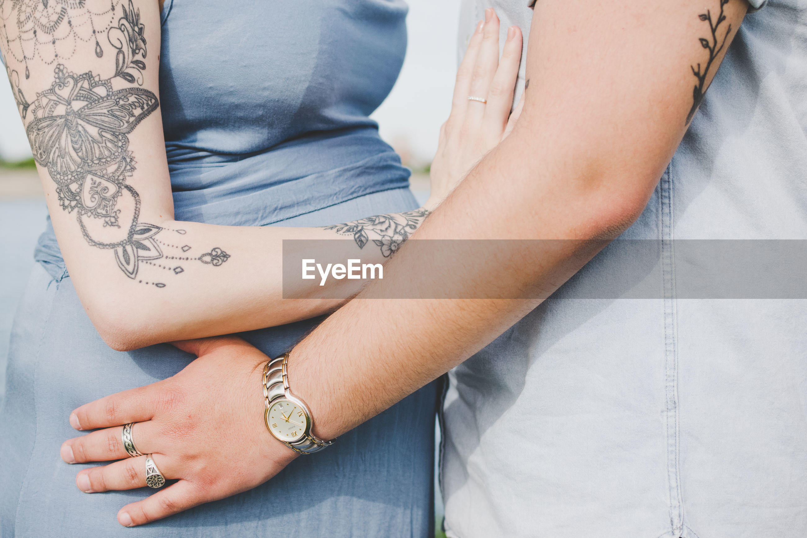 MIDSECTION OF COUPLE HOLDING HANDS WITH TATTOO