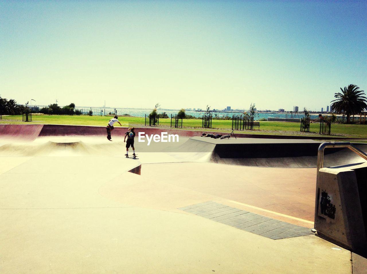 Rear view of two people skateboarding on ramp