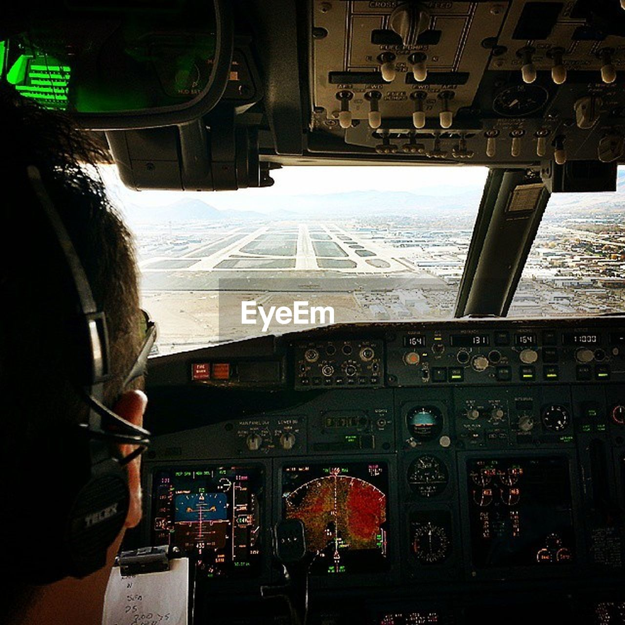 cockpit, vehicle interior, airplane, pilot, control panel, transportation, piloting, dashboard, flying, air vehicle, control, co-pilot, windshield, mode of transport, travel, commercial airplane, occupation, aerospace industry, gauge, day, technology, adult, adults only, speedometer, indoors, one person, people, sky