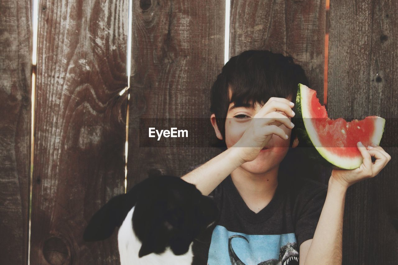 CLOSE-UP PORTRAIT OF CUTE BOY EATING FRUIT