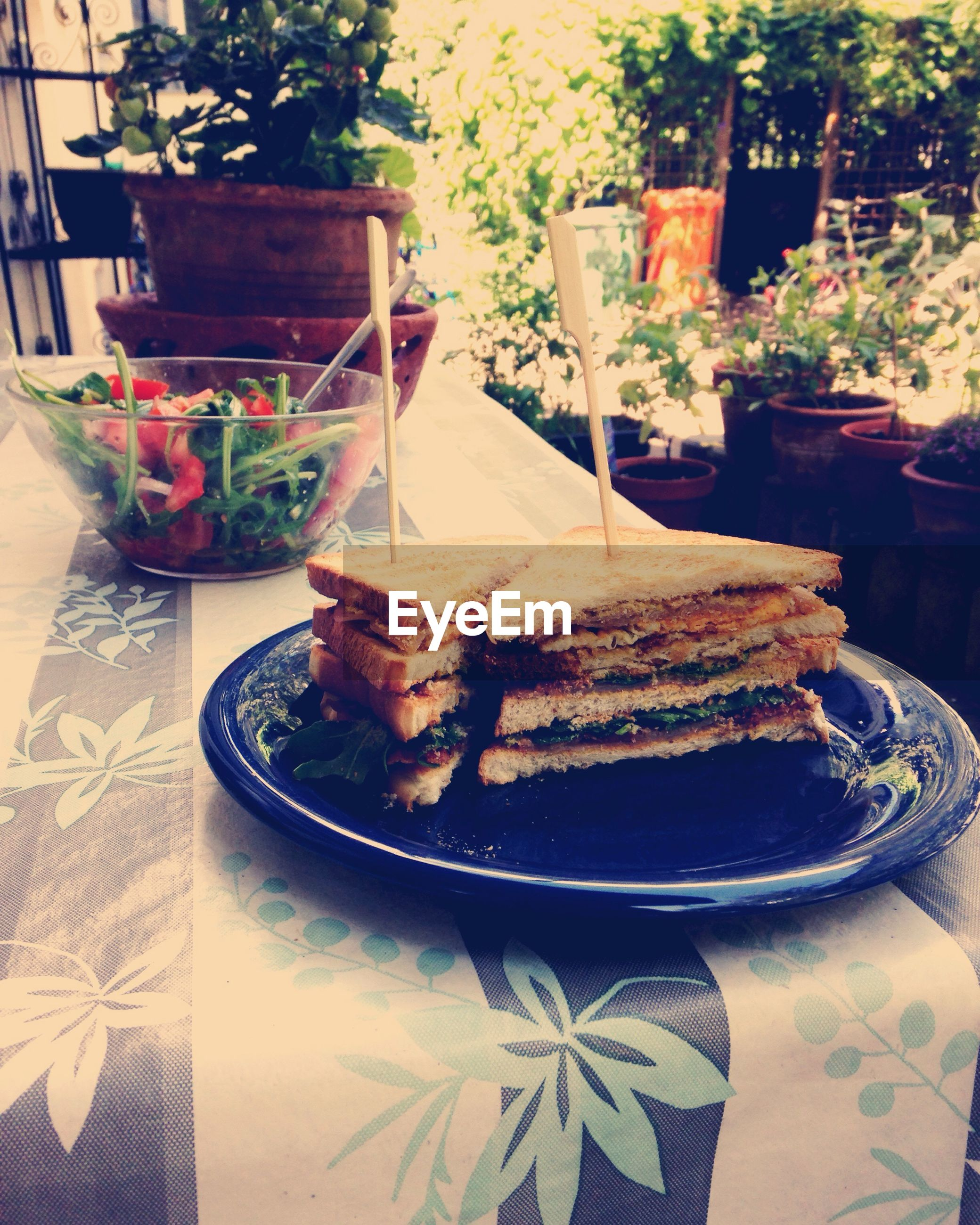 table, food and drink, freshness, drink, food, still life, high angle view, potted plant, chair, refreshment, sunlight, indoors, drinking glass, restaurant, day, no people, absence, ready-to-eat, plate, serving size
