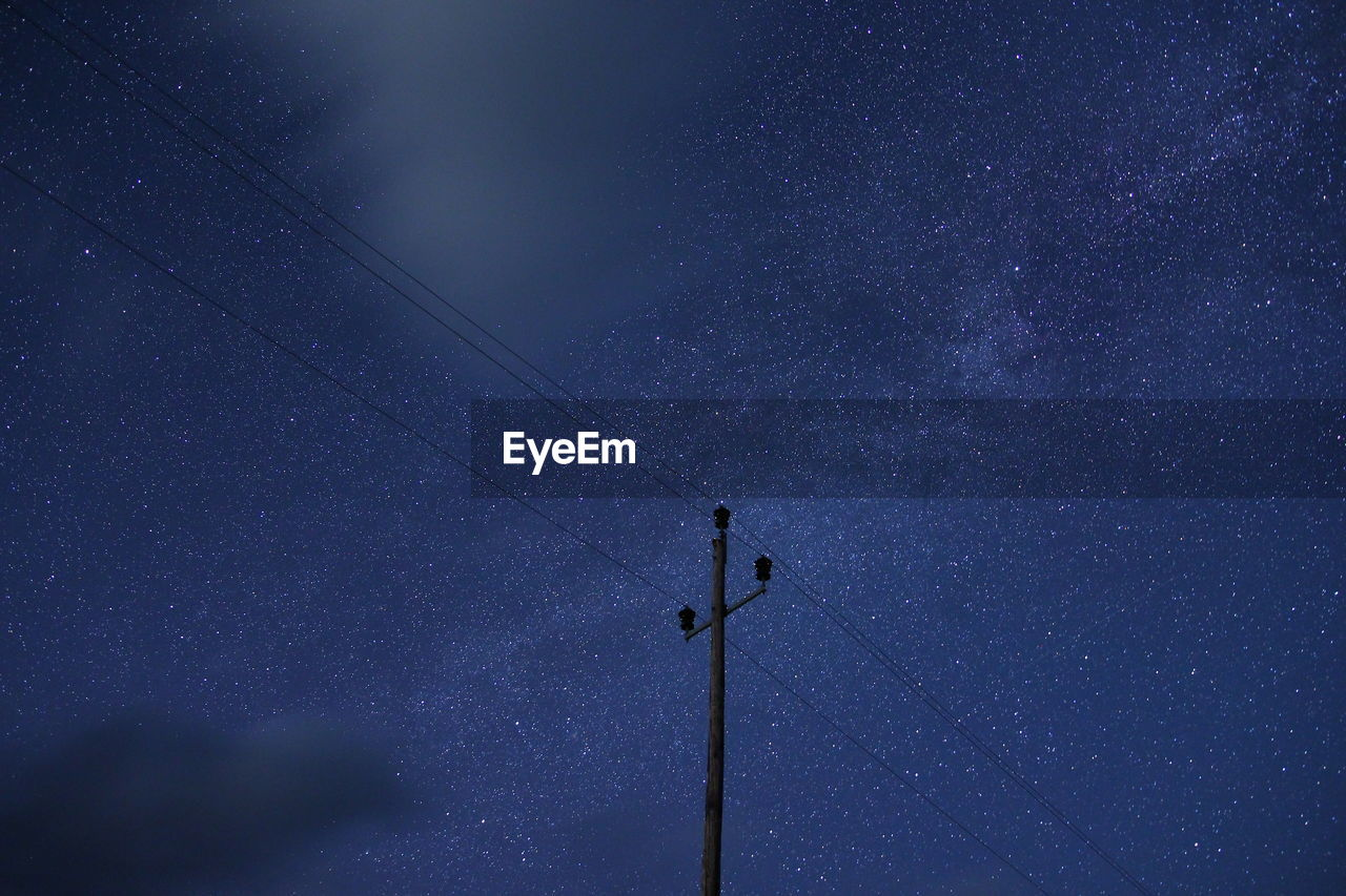 Low Angle View Of Electricity Pylon Against Star Field At Night