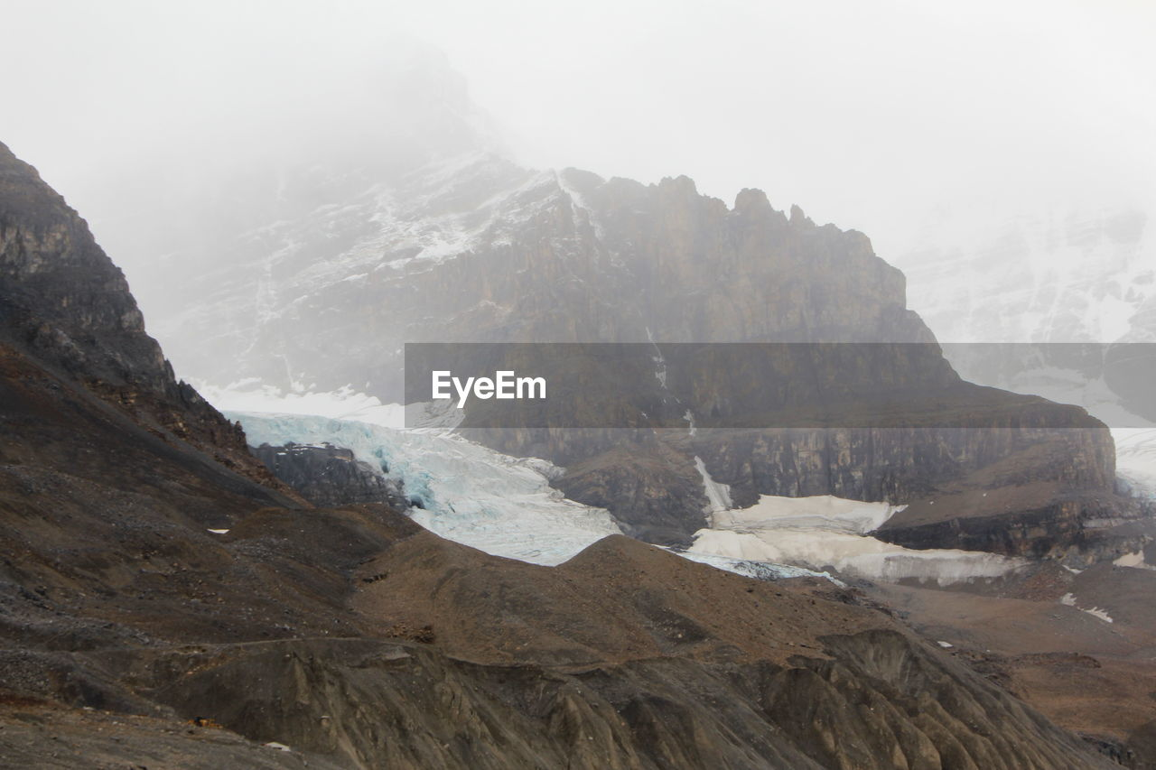 mountain, environment, fog, beauty in nature, landscape, nature, cold temperature, sky, mountain peak, scenery, snow, no people, water, winter, scenics - nature, wilderness, rock, mountain range, day, outdoors, formation, height, high