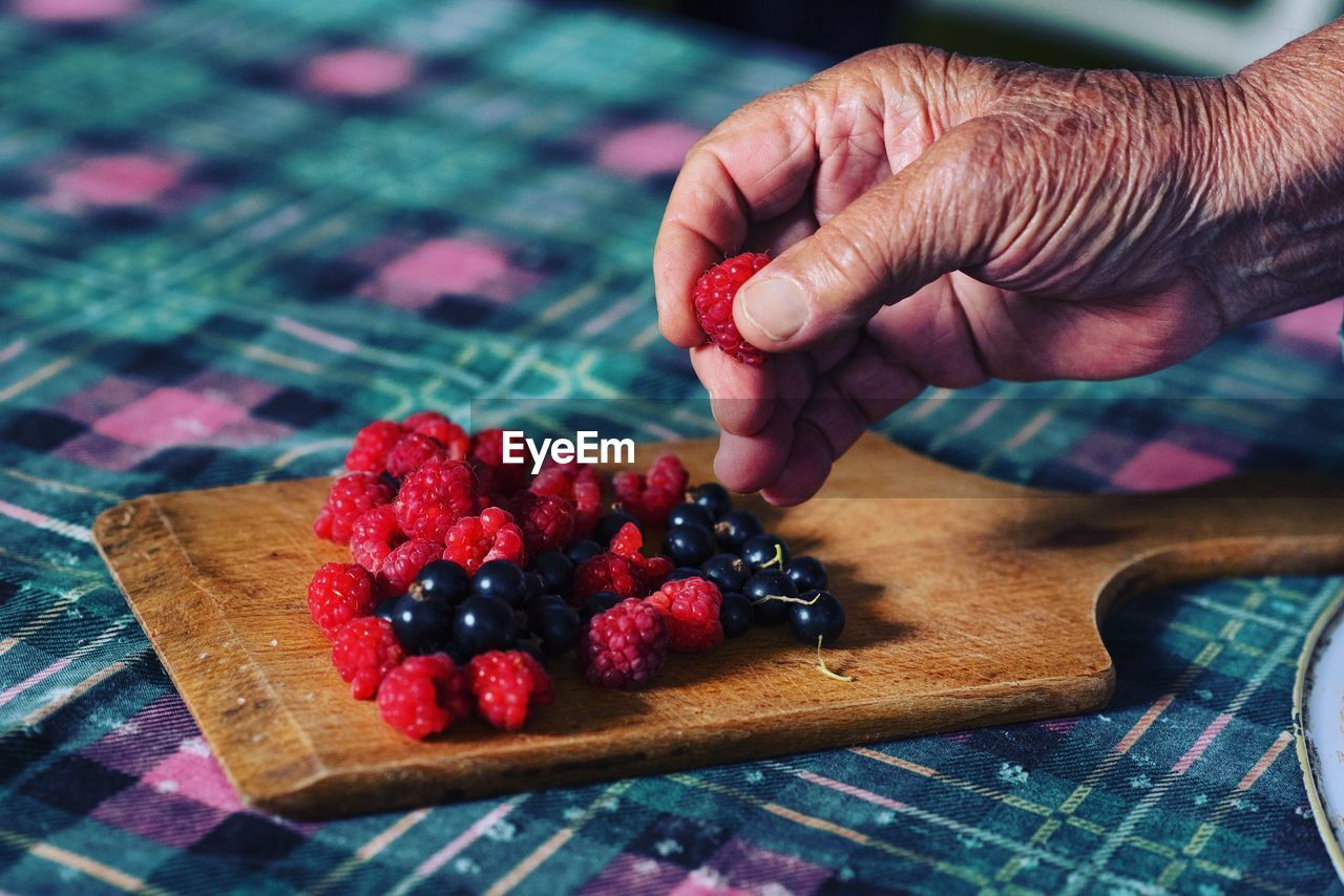 Cropped Hand Arranging Berries On Serving Board