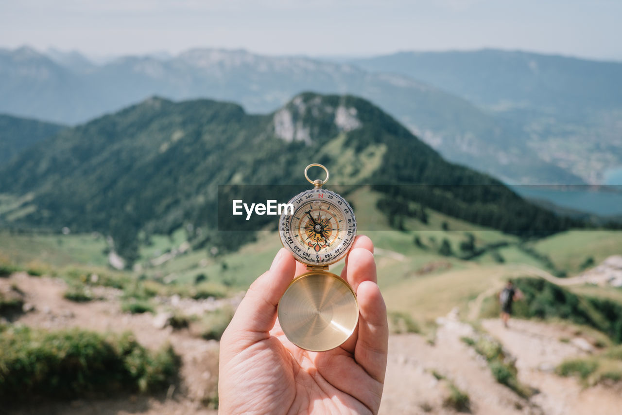 Cropped Hand Holding Compass Against Mountains