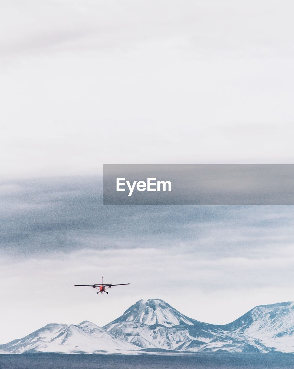 Helicopter flying over lake against snowcapped mountains