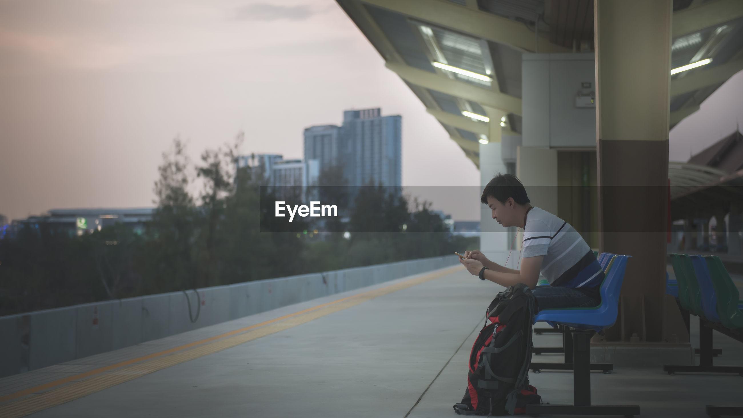 Man using phone while sitting on seat