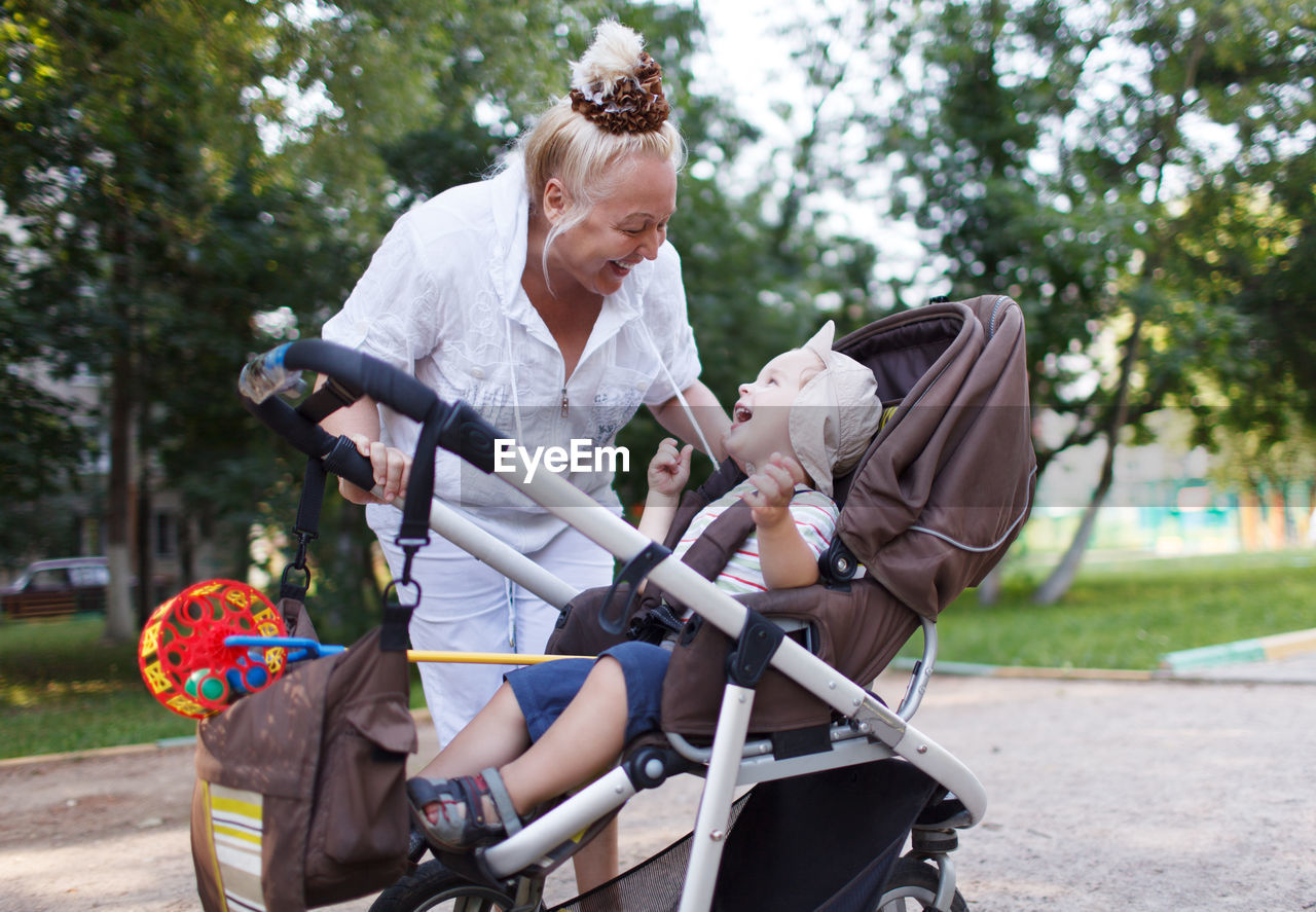 Happy grandmother with grandson in carriage on footpath at park