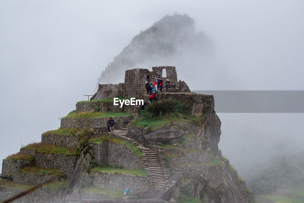 fog, mountain, travel, tourism, sky, men, nature, real people, group of people, leisure activity, lifestyles, history, travel destinations, day, architecture, people, tourist, geology, the past, outdoors, ancient civilization, formation