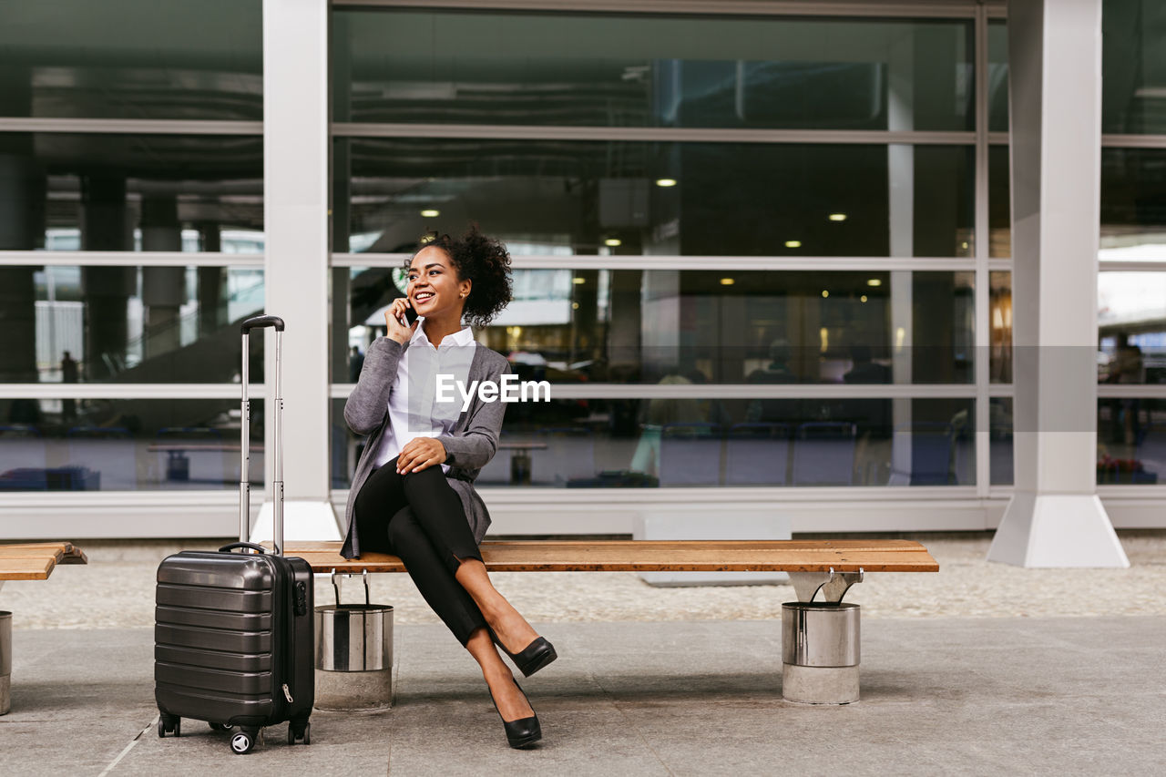 Close-Up Of Businesswoman Talking On Phone While Sitting On Bench