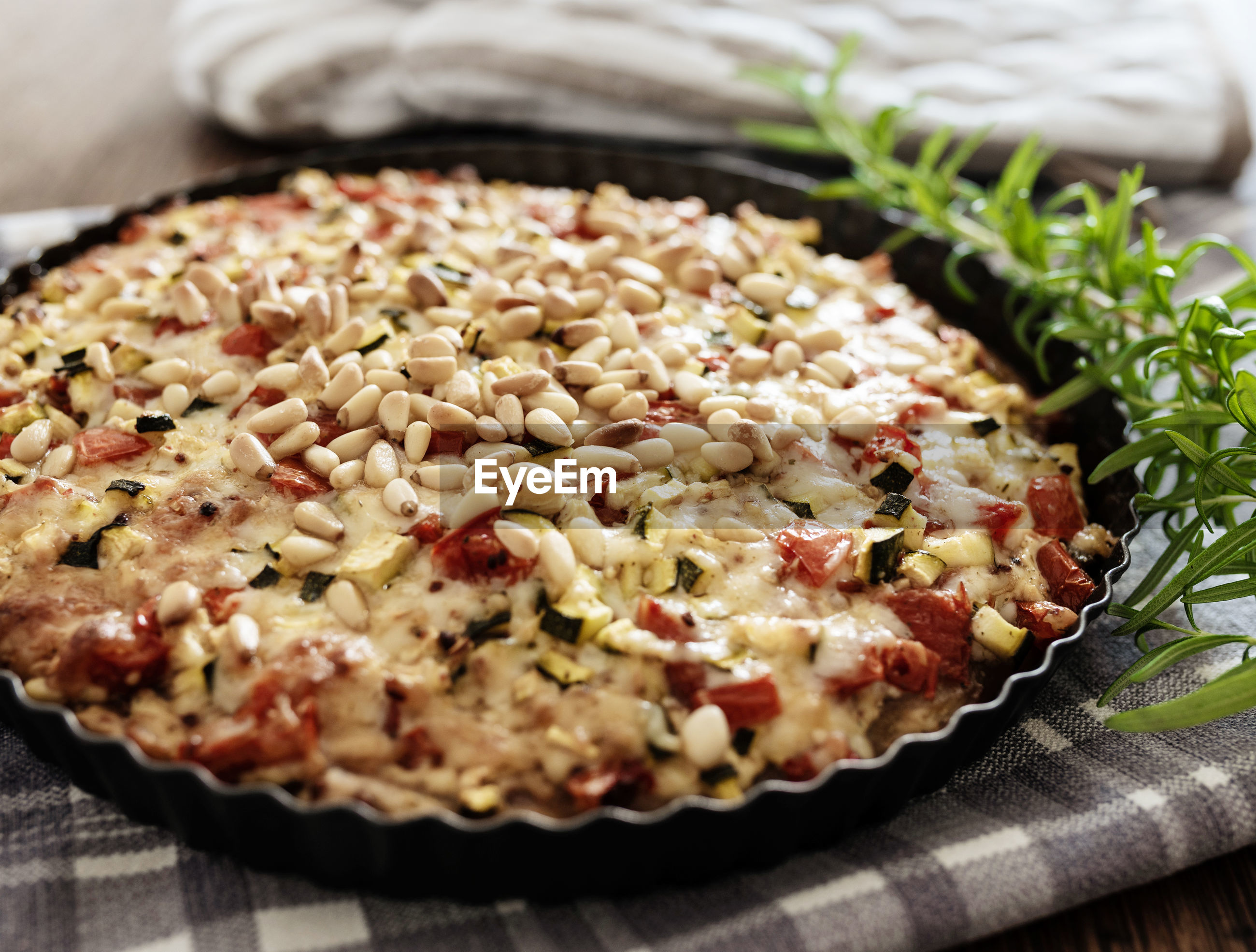 Close-up of pizza in baking sheet on table