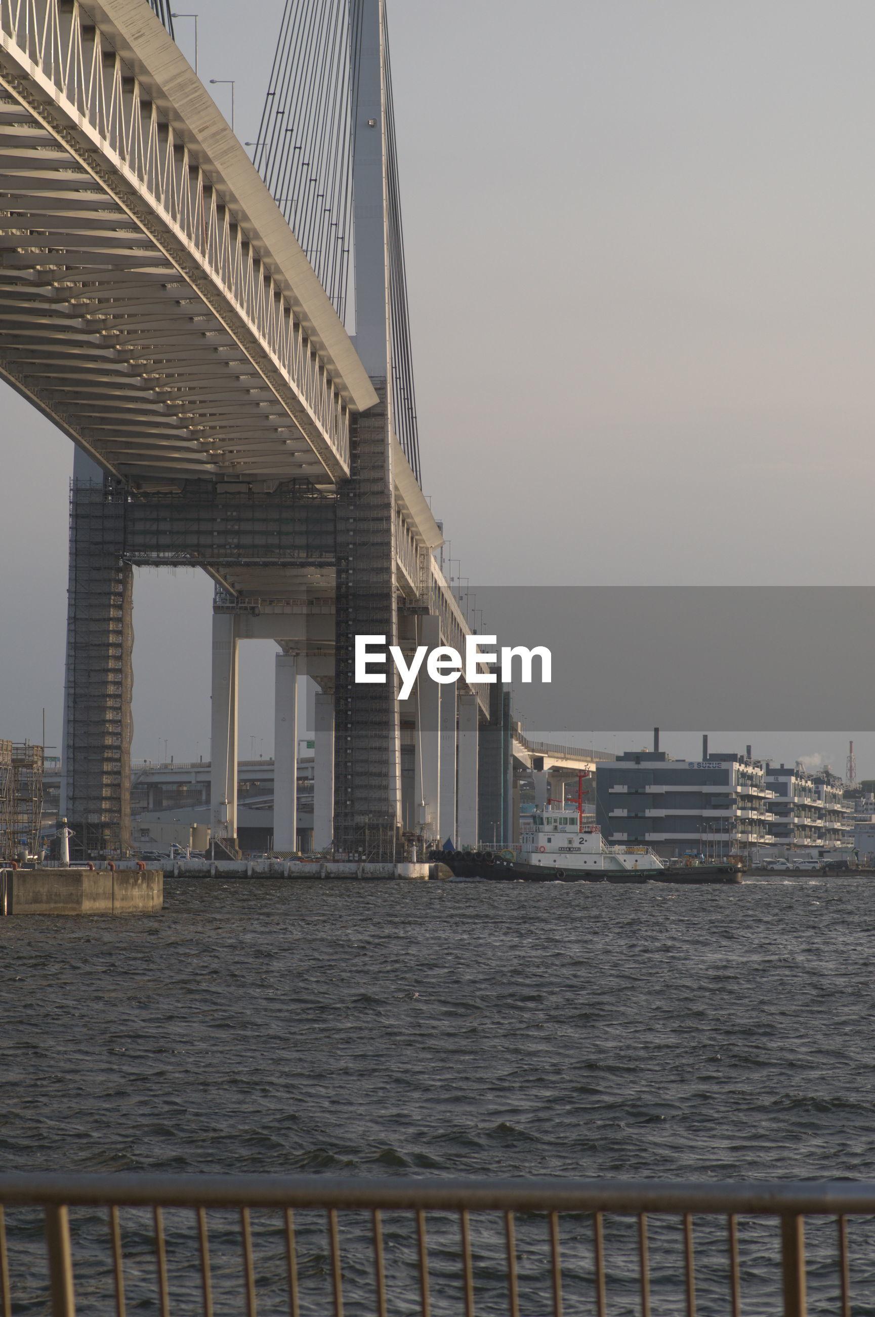 Bridge over sea by buildings against sky in city