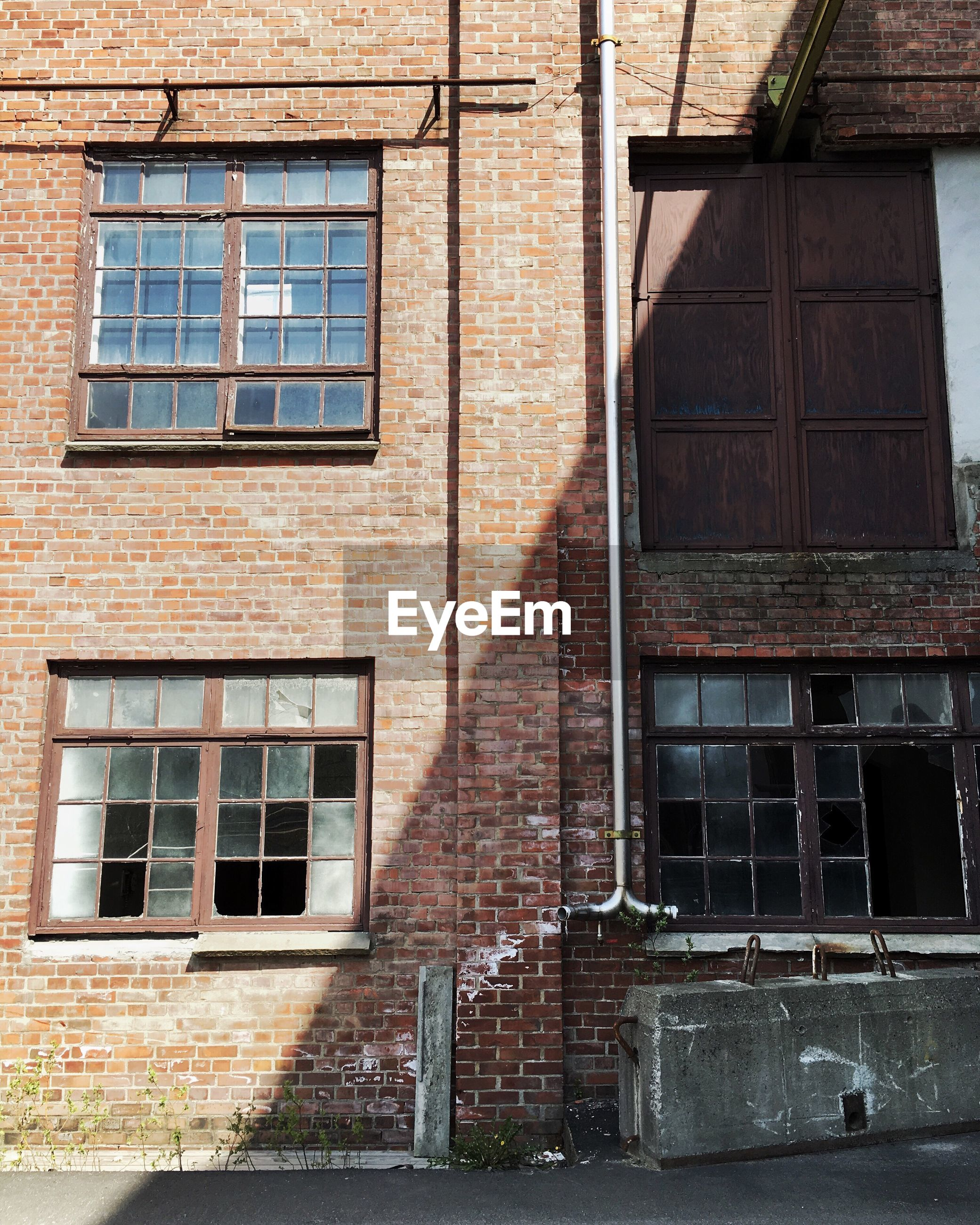architecture, building exterior, built structure, window, low angle view, building, brick wall, residential building, residential structure, old, house, glass - material, day, outdoors, wall - building feature, no people, exterior, city, weathered, wall