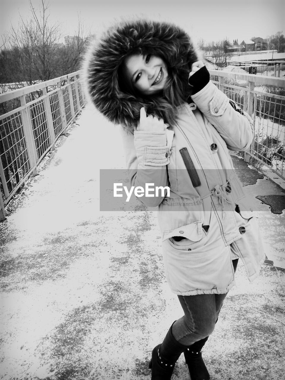 Portrait of happy woman wearing fake fur jacket while standing on elevated walkway during winter