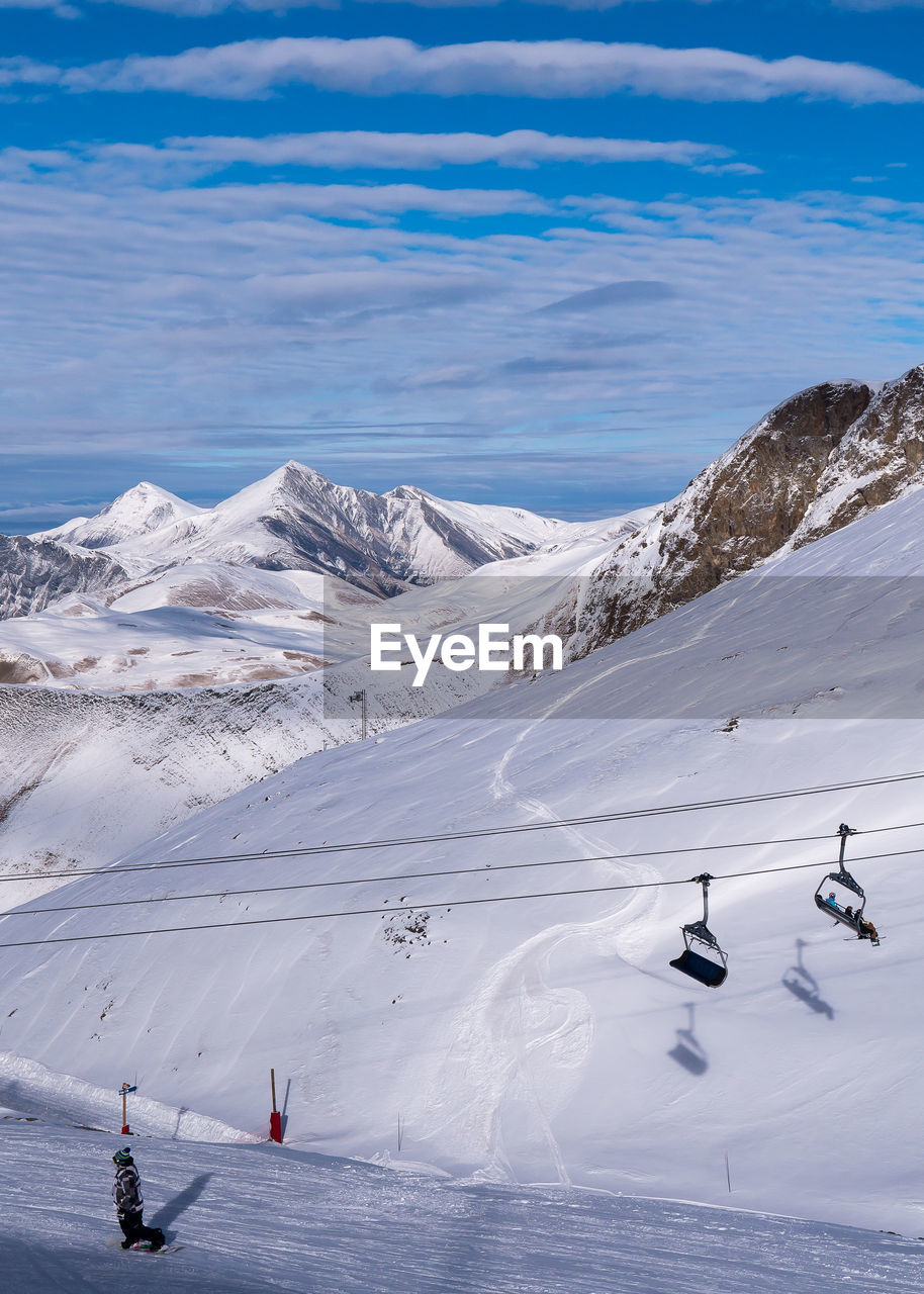 Overhead Cable Cars By Snow Covered Mountains Against Cloudy Sky