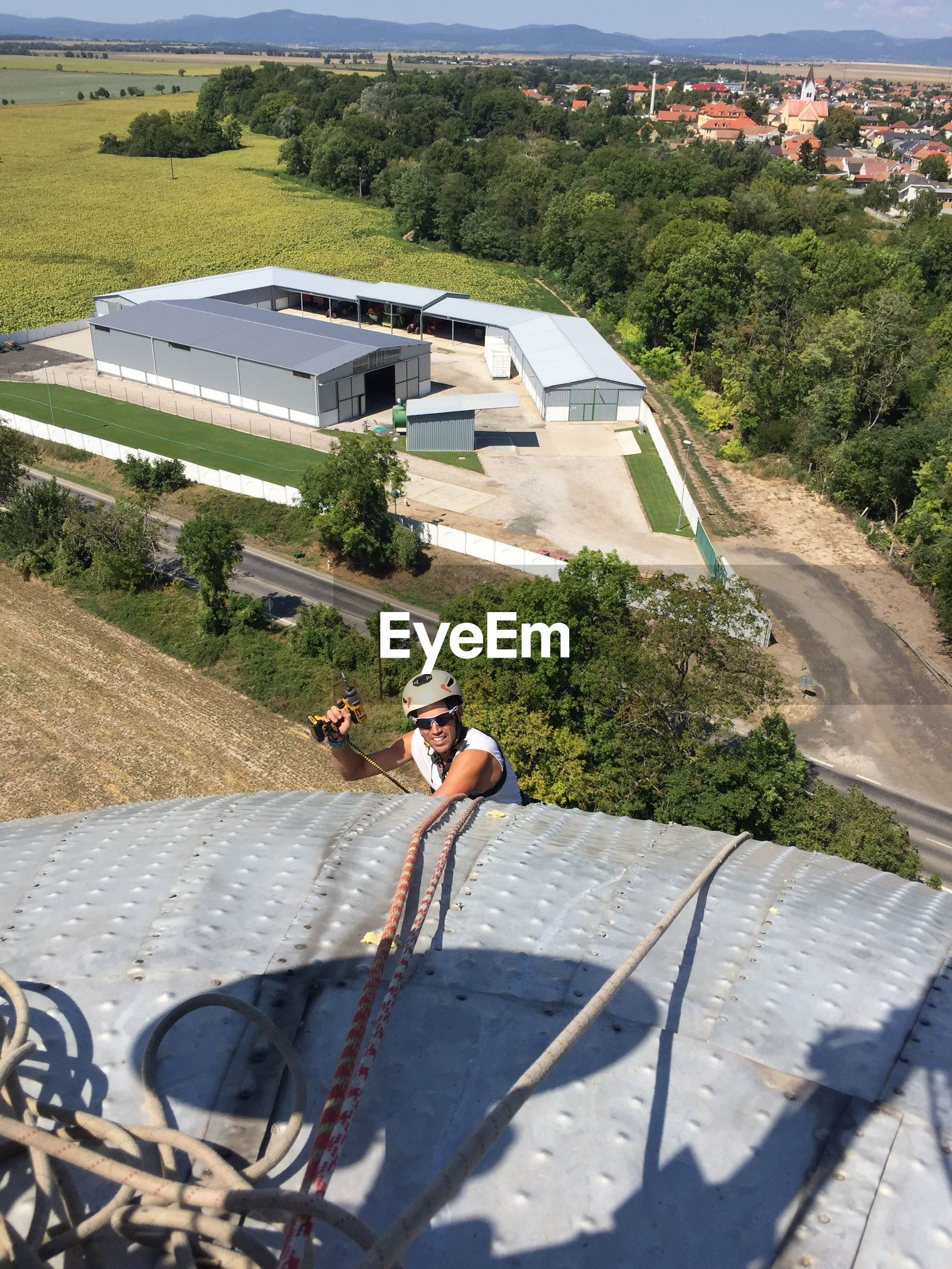 High angle view of man climbing on built structure during sunny day