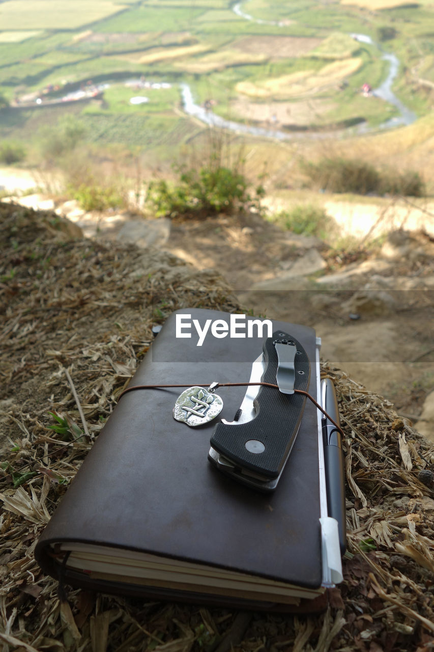 High angle view of penknife with diary on field