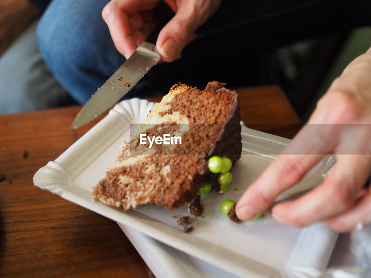 Close-Up Of Man Holding Knife And Cake