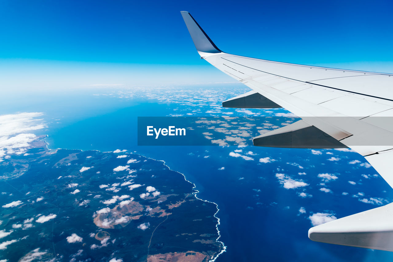 air vehicle, airplane, mode of transportation, flying, transportation, blue, aircraft wing, mid-air, sky, travel, no people, nature, scenics - nature, beauty in nature, motion, day, aerial view, cloud - sky, sea, journey, outdoors