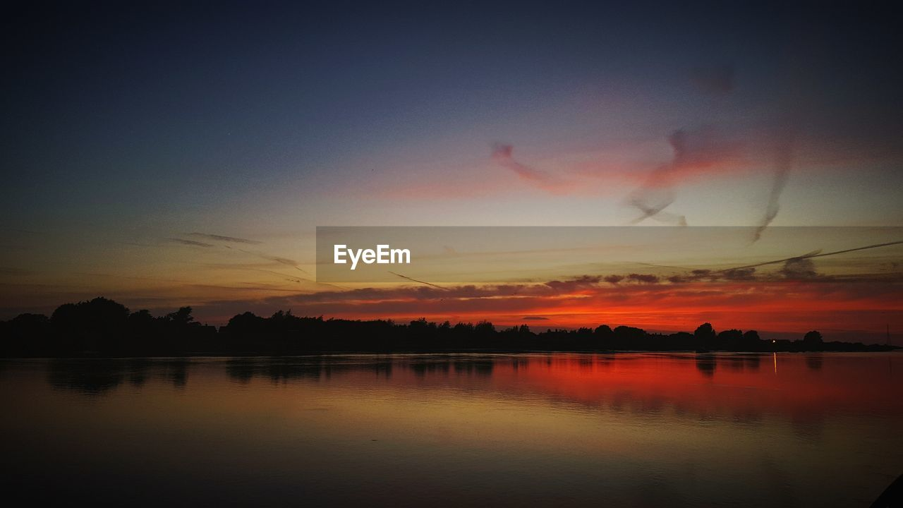 sky, sunset, scenics - nature, water, beauty in nature, tranquility, orange color, tranquil scene, lake, reflection, cloud - sky, nature, idyllic, waterfront, silhouette, no people, outdoors, tree, non-urban scene, romantic sky