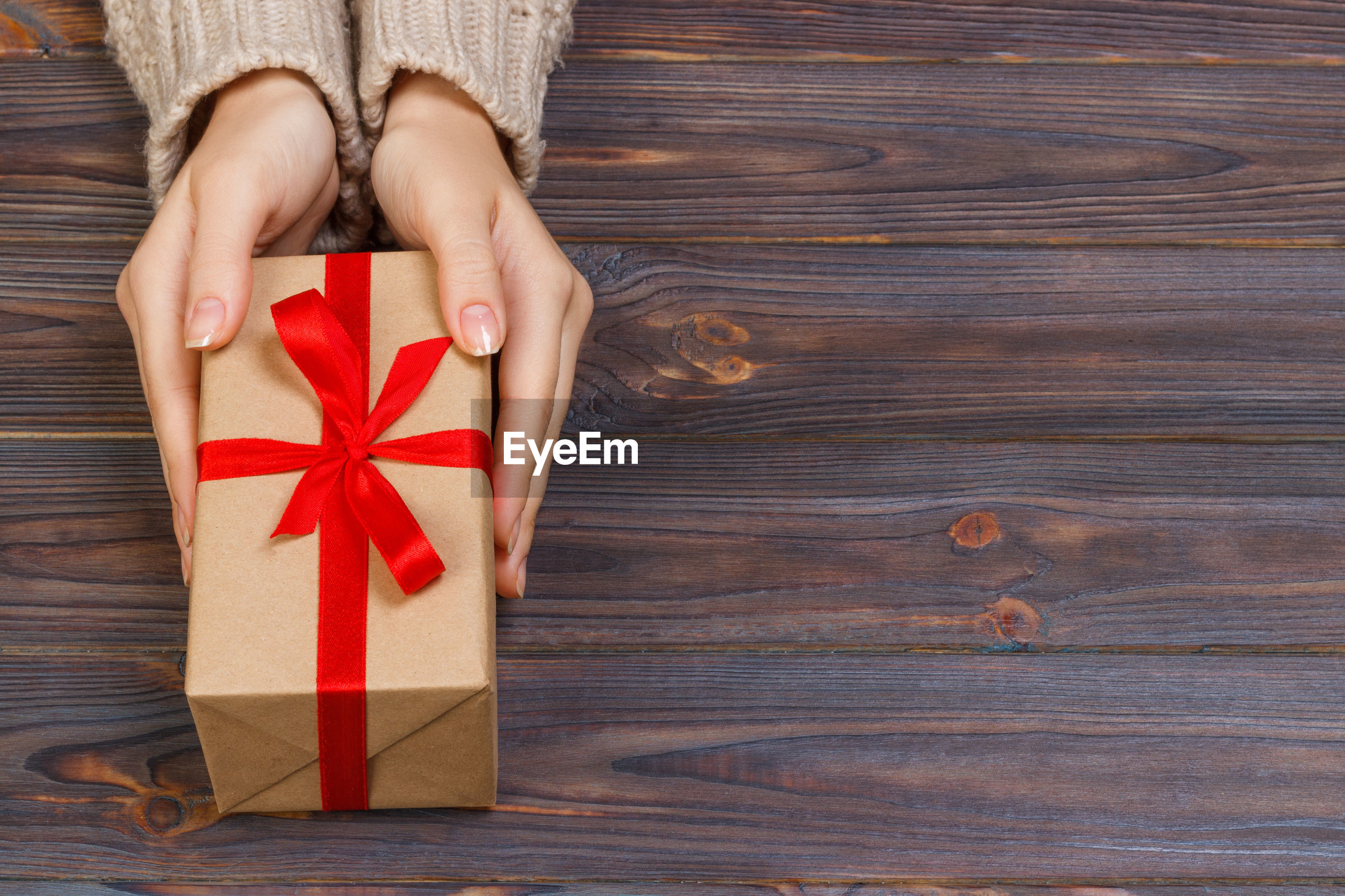Cropped hands of woman holding gift box on table