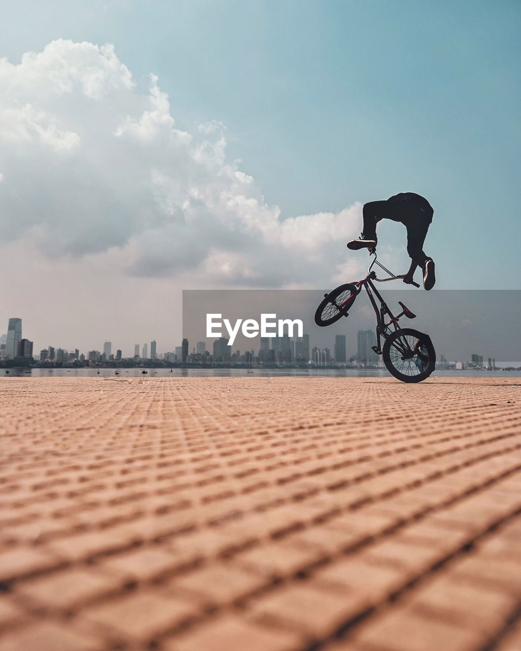 bicycle, sky, transportation, cloud - sky, mode of transportation, nature, land vehicle, surface level, sport, day, city, leisure activity, architecture, one person, lifestyles, outdoors, real people, selective focus, ride, built structure, riding