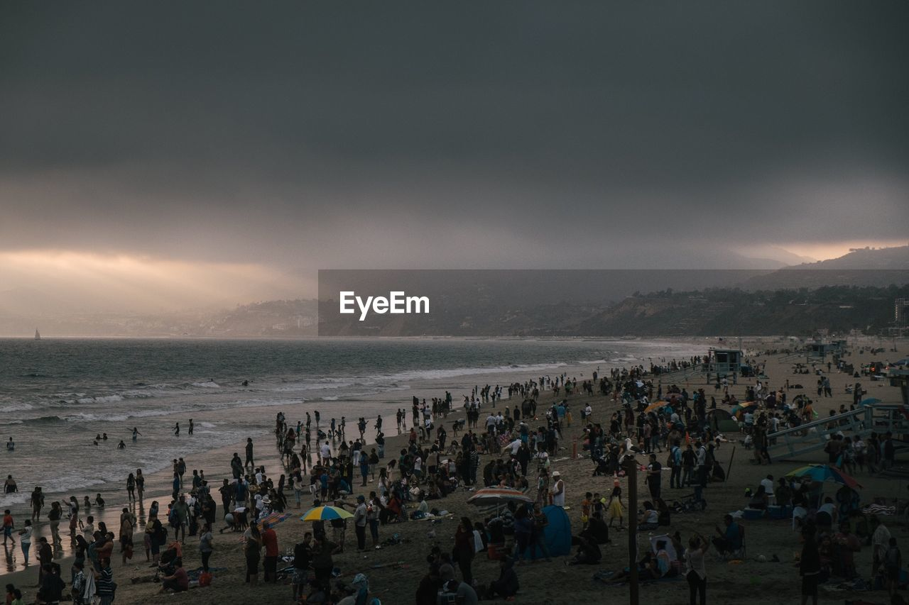 People At Beach Against Cloudy Sky During Sunset