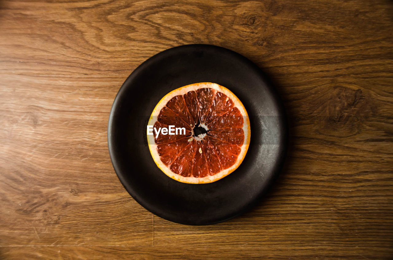table, food and drink, indoors, still life, high angle view, directly above, freshness, food, healthy eating, fruit, wood - material, no people, cross section, close-up, sweet food, blood orange, day