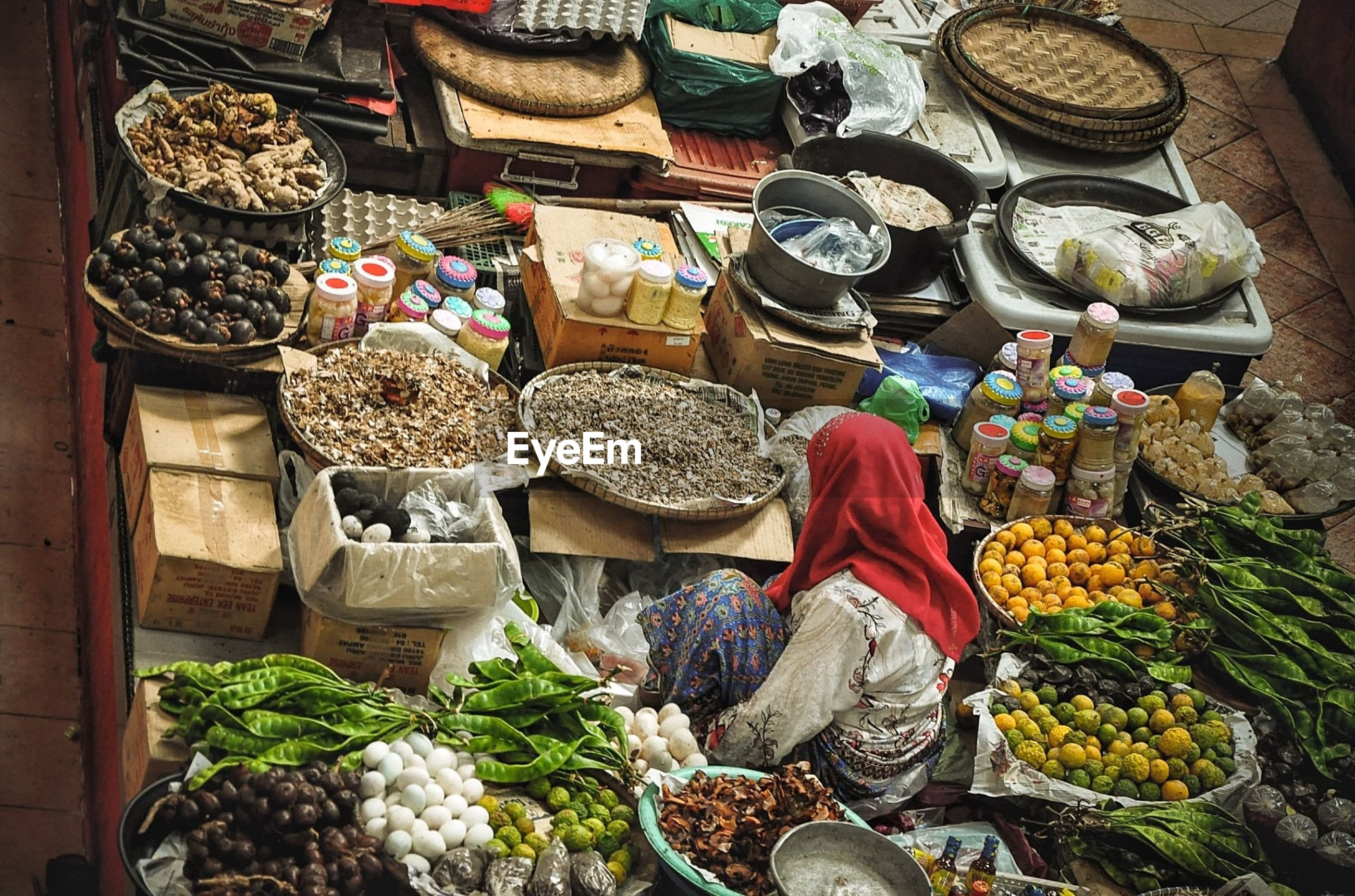 Vendor with various food for sale at market stall