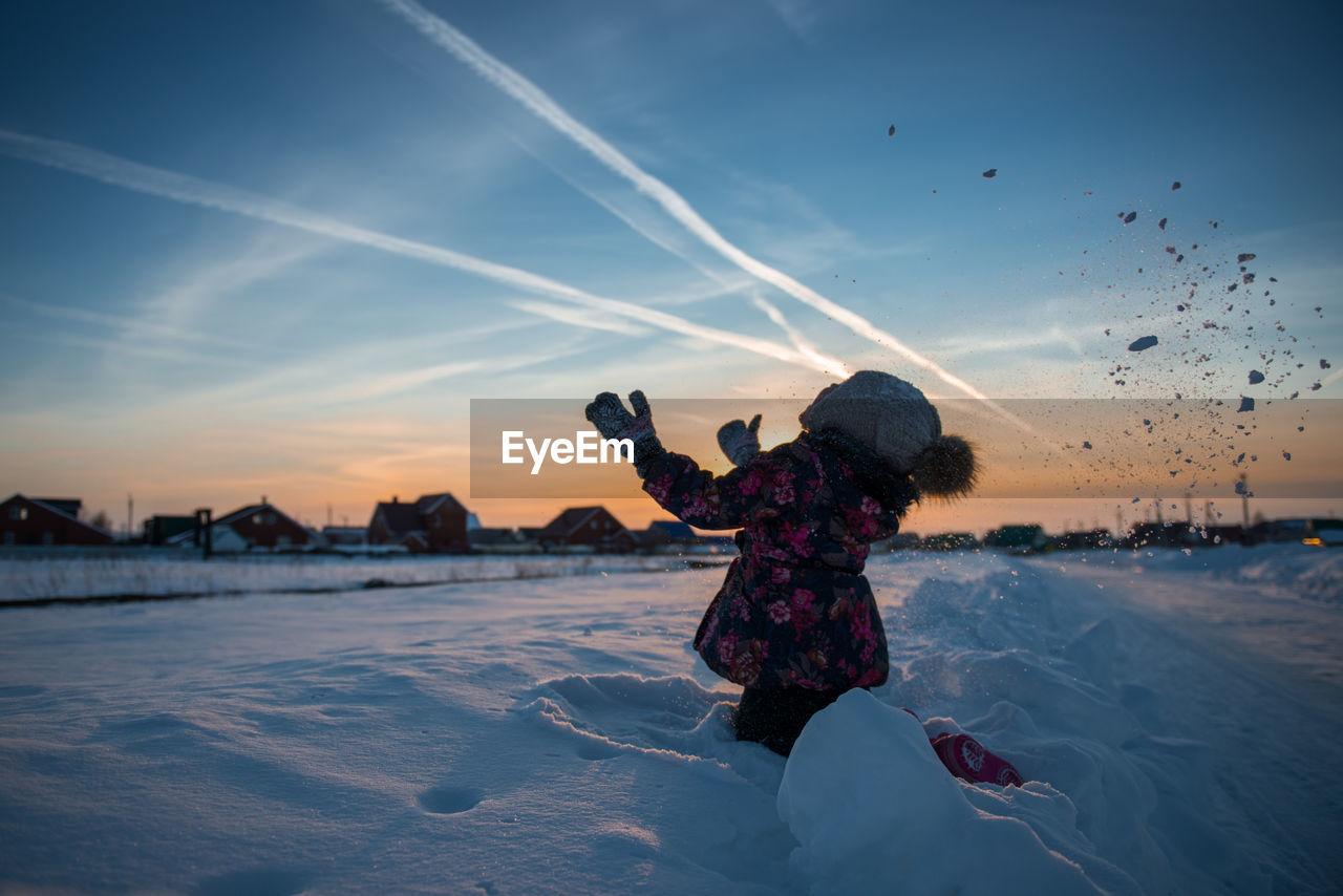 Full length of girl on snow covered land against sky during sunset