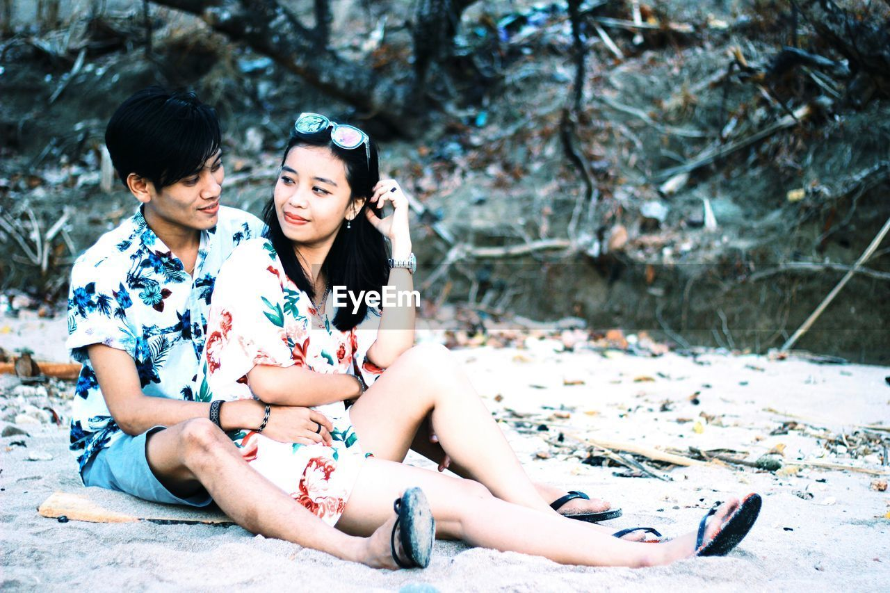 real people, young adult, sitting, two people, young women, full length, togetherness, leisure activity, women, lifestyles, casual clothing, nature, focus on foreground, people, young men, adult, day, front view, tree, couple - relationship, outdoors, hairstyle