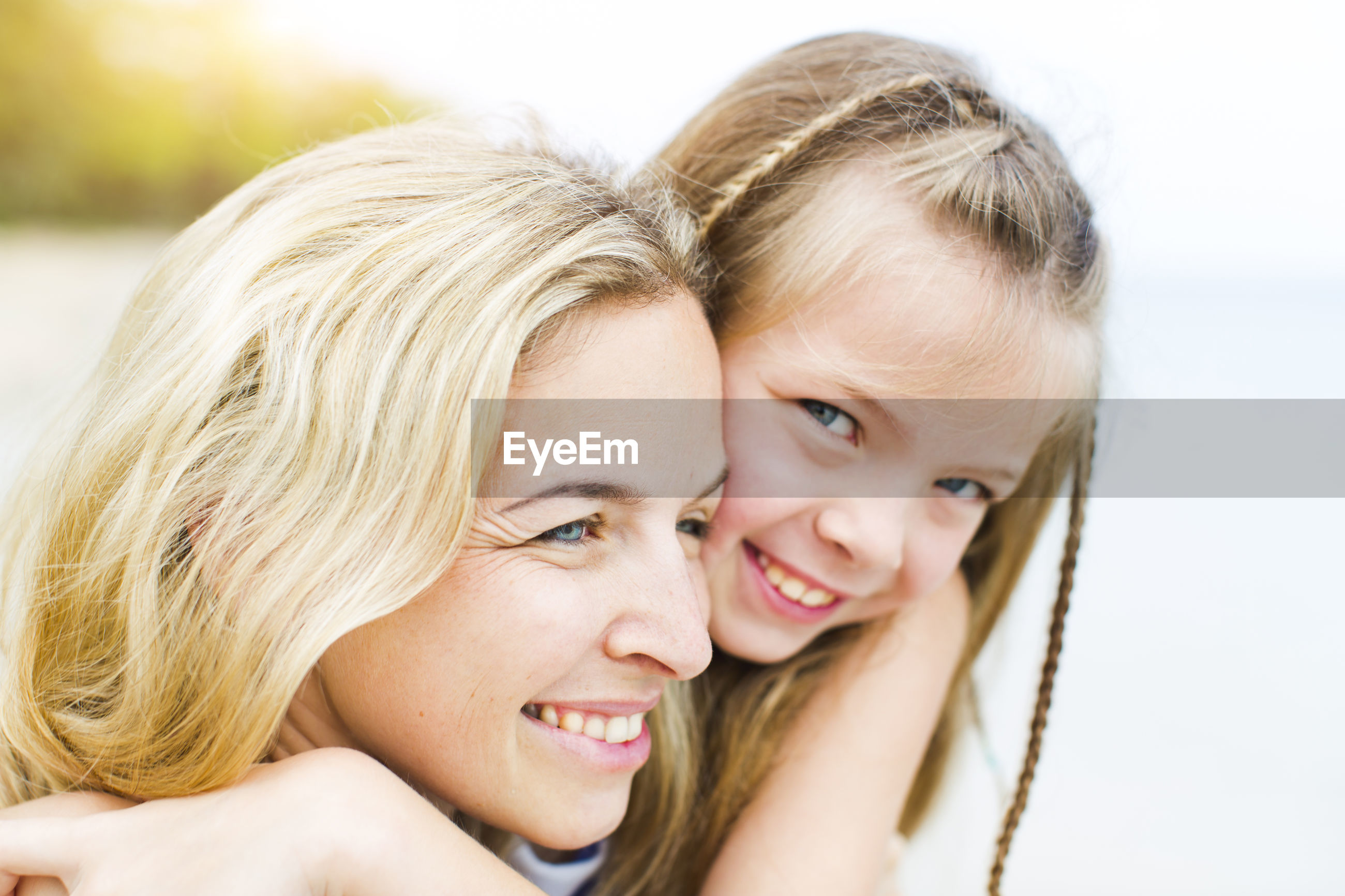 Close-up portrait of smiling girl with mother at beach