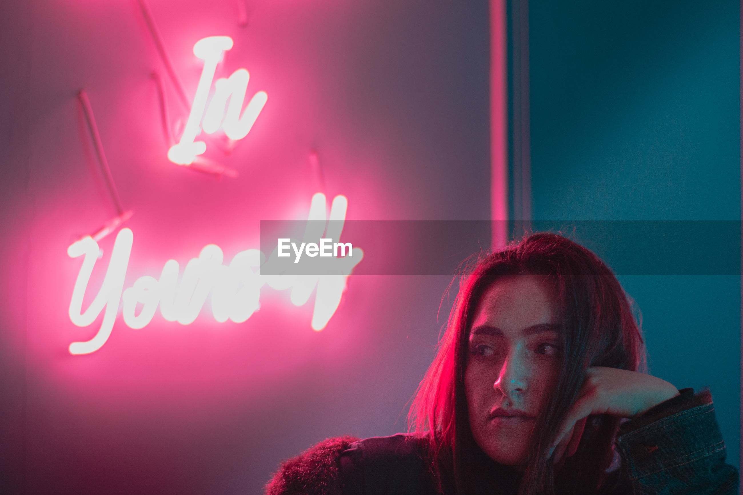 Thoughtful young woman sitting against pink neon text on wall