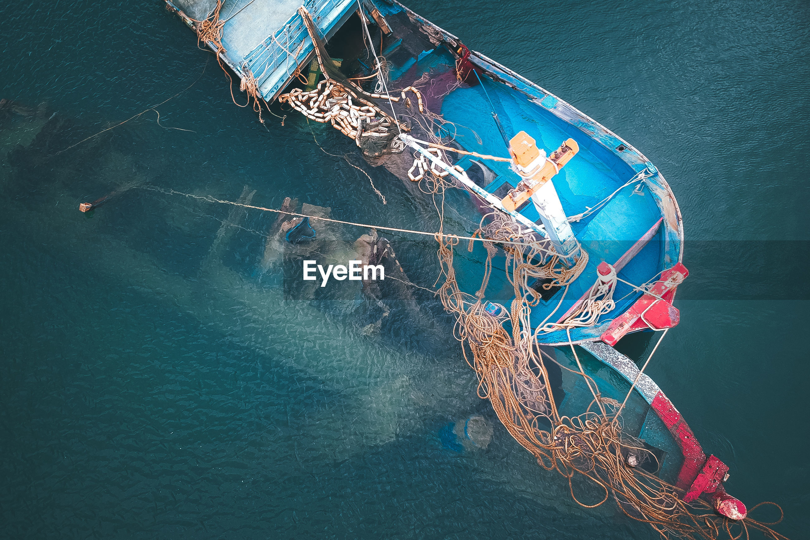 HIGH ANGLE VIEW OF FISHING BOAT MOORED AT SEA
