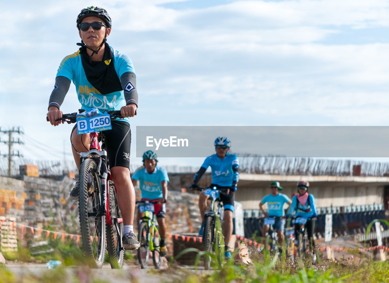 bicycle, cycling, cycling helmet, real people, lifestyles, leisure activity, riding, sky, adventure, sport, outdoors, helmet, healthy lifestyle, full length, day, cloud - sky, headwear, sports clothing, men, exercising, racing bicycle, mountain bike, nature, extreme sports, sports helmet, sports race, women, sportsman, athlete, young adult, young women, triathlon, people